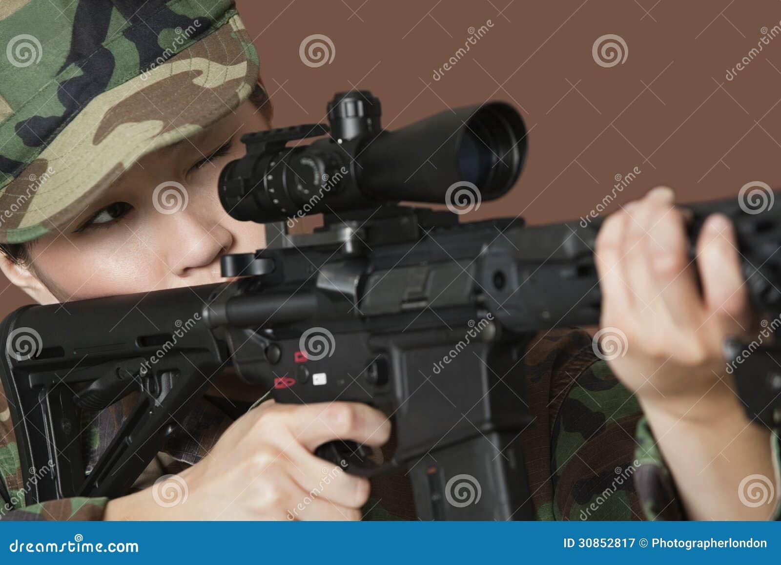 Молодой солдат морской пехот США женщины направляя штурмовую винтовку M4 над коричневой предпосылкой
