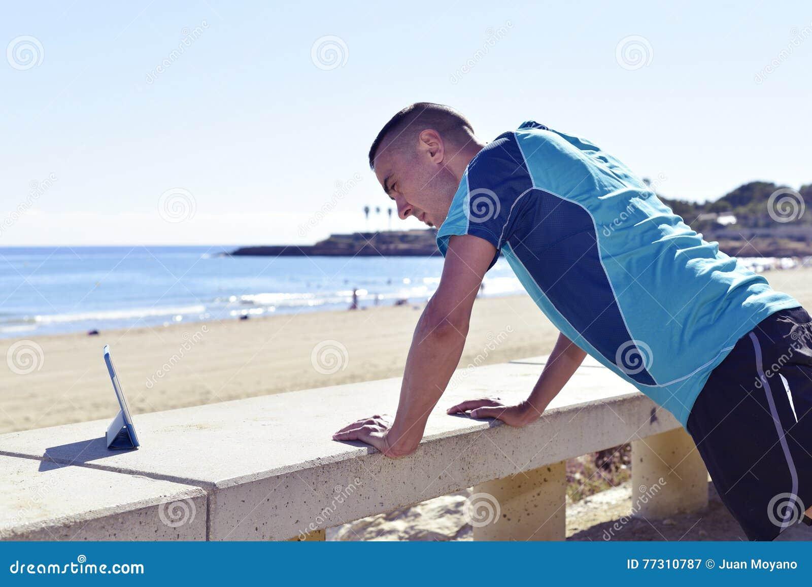 Молодой спортсмен делая уклон нажим-поднимает