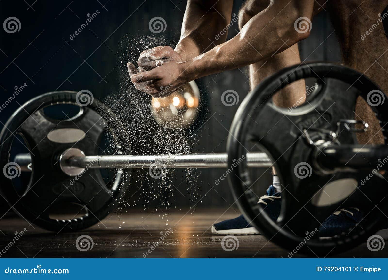 Молодой спортсмен получая готовый для тренировки поднятия тяжестей Рука Powerlifter в тальке подготавливая к жиму лёжа