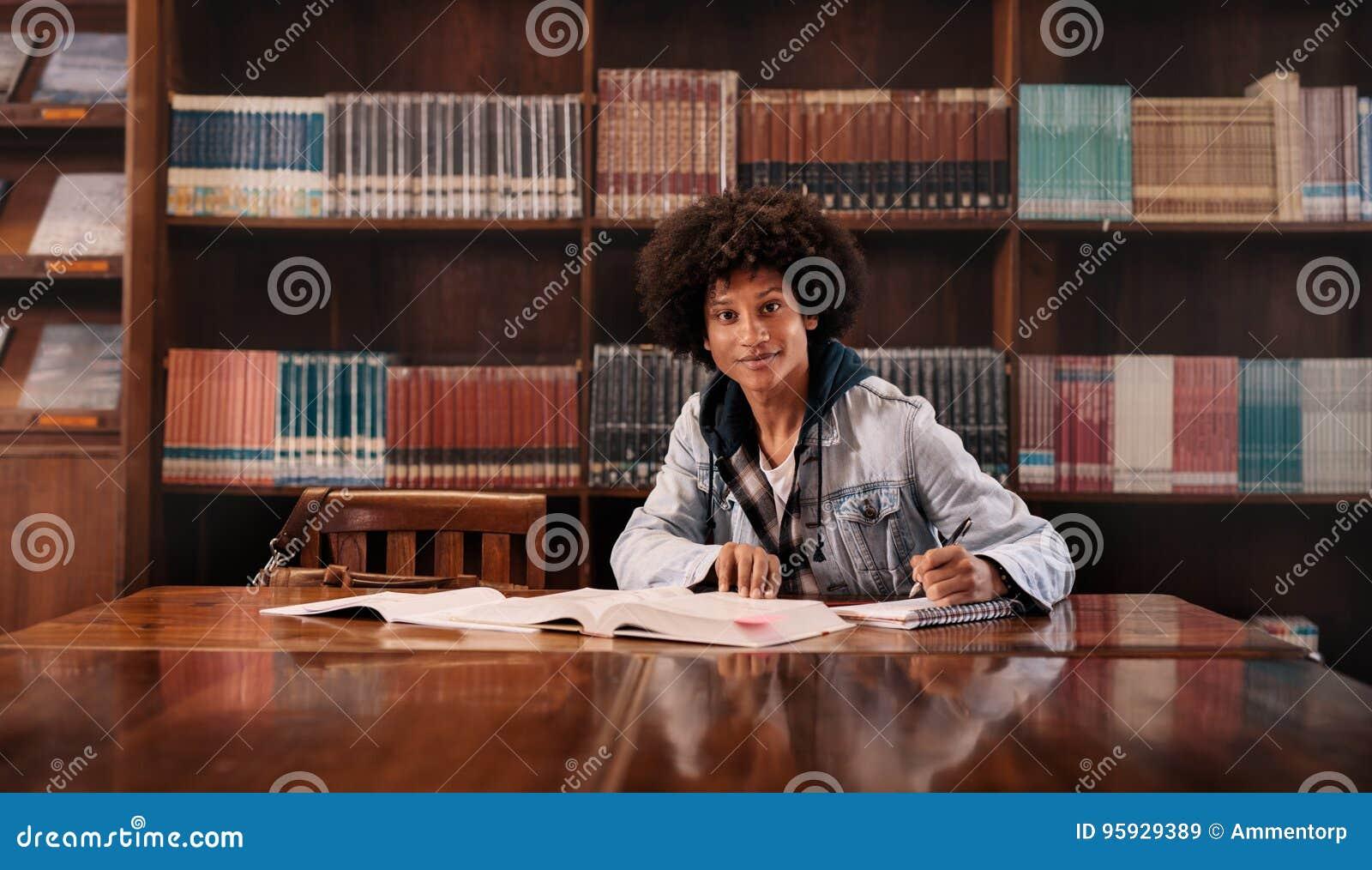 Молодой студент колледжа делая домашнюю работу в библиотеке