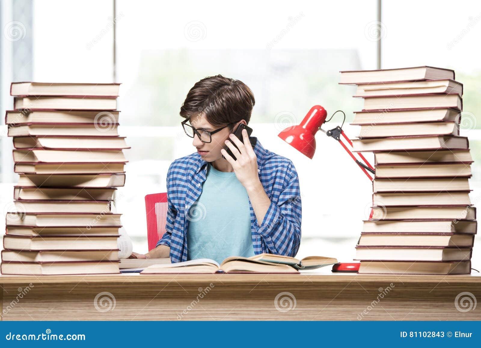 Молодой студент подготавливая для экзаменов школы