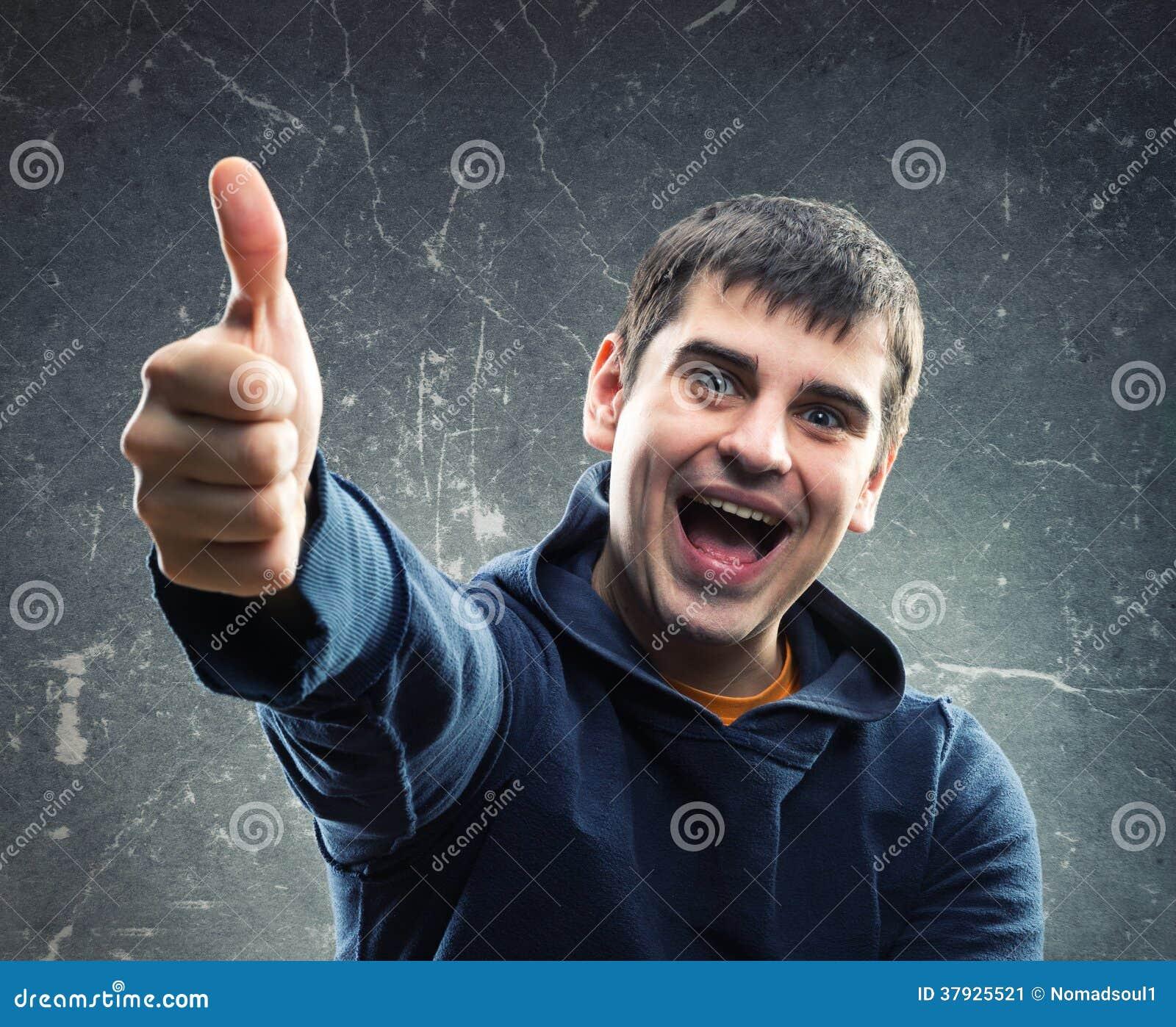 Молодой человек давая большой палец руки вверх