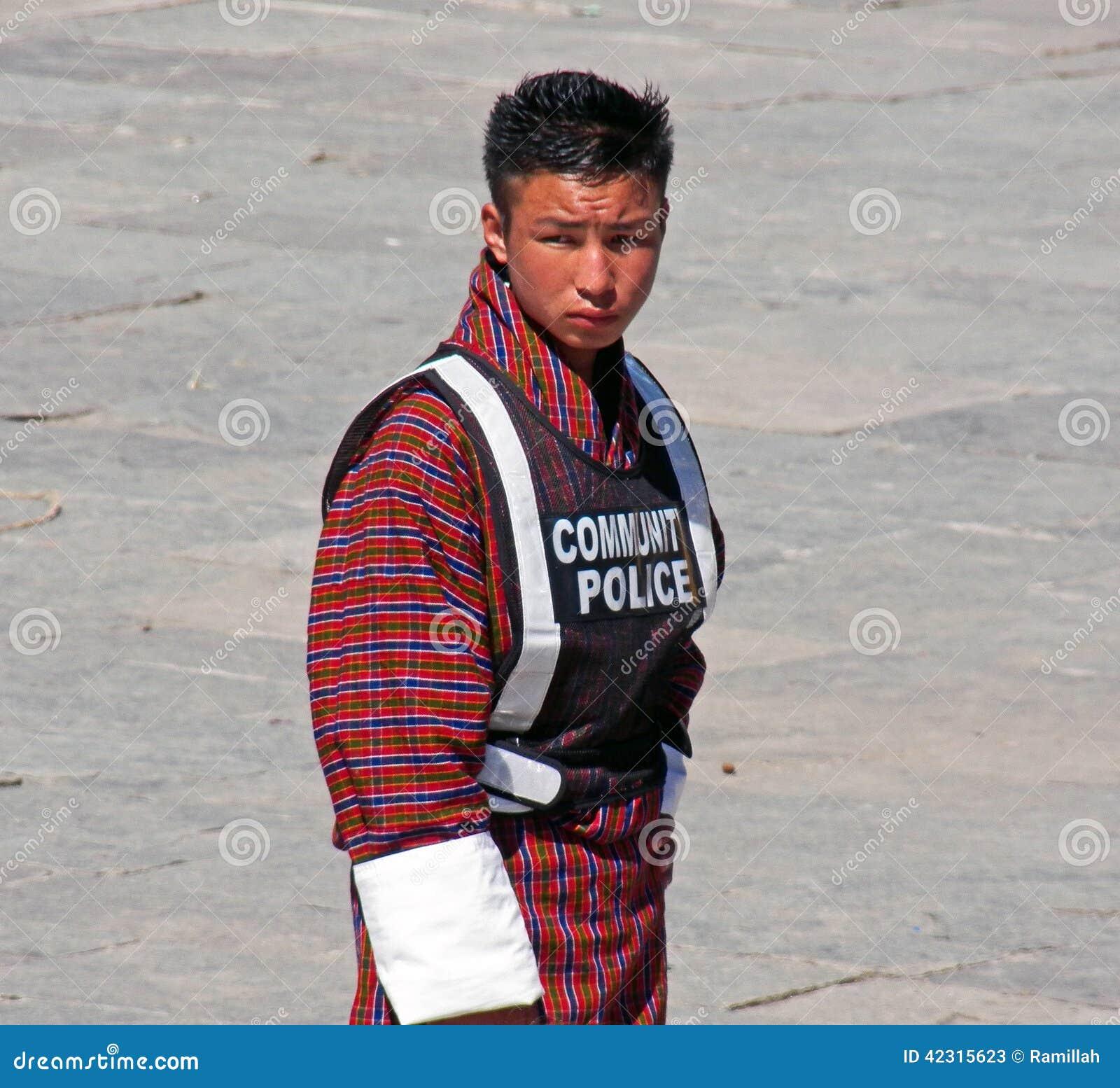 Молодой человек вызывался добровольцем как полиция общины на фестивале Wangdue Tshechu