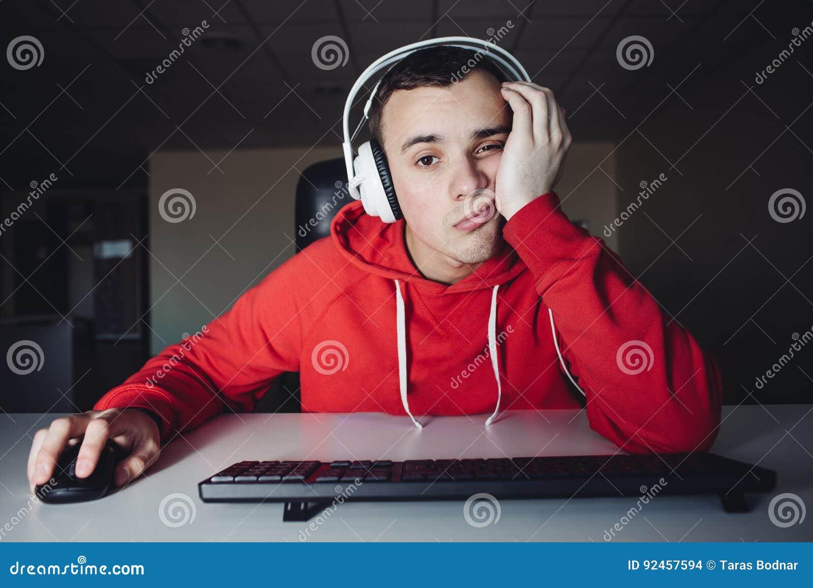 Молодой человек в компьютерах пользы наушников на ноче Gamer играет игры на компьютере