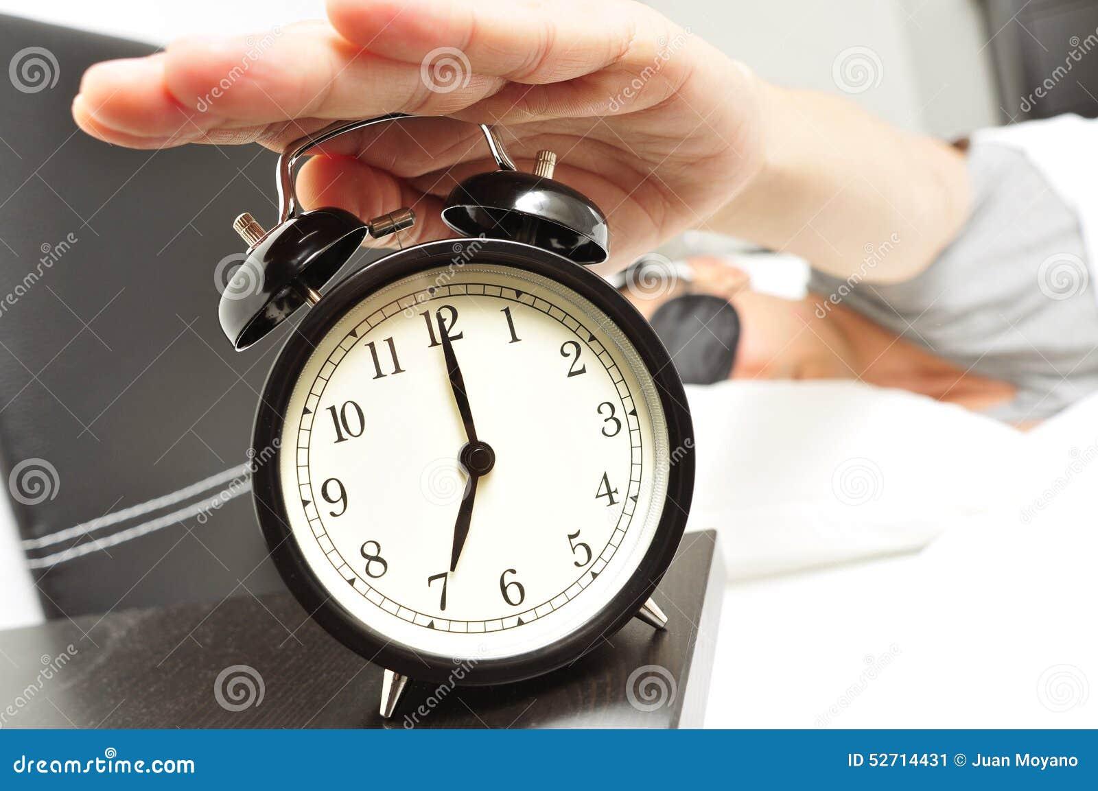 Молодой человек в кровати при маска сна останавливая будильник