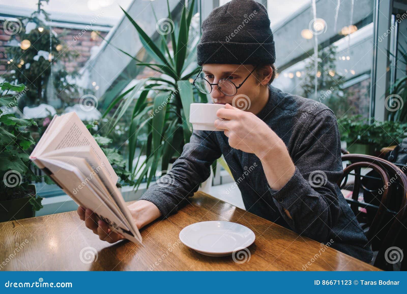 Молодой человек в крышке и рубашке читая книгу и выпивая кофе в ресторане с консерваторией