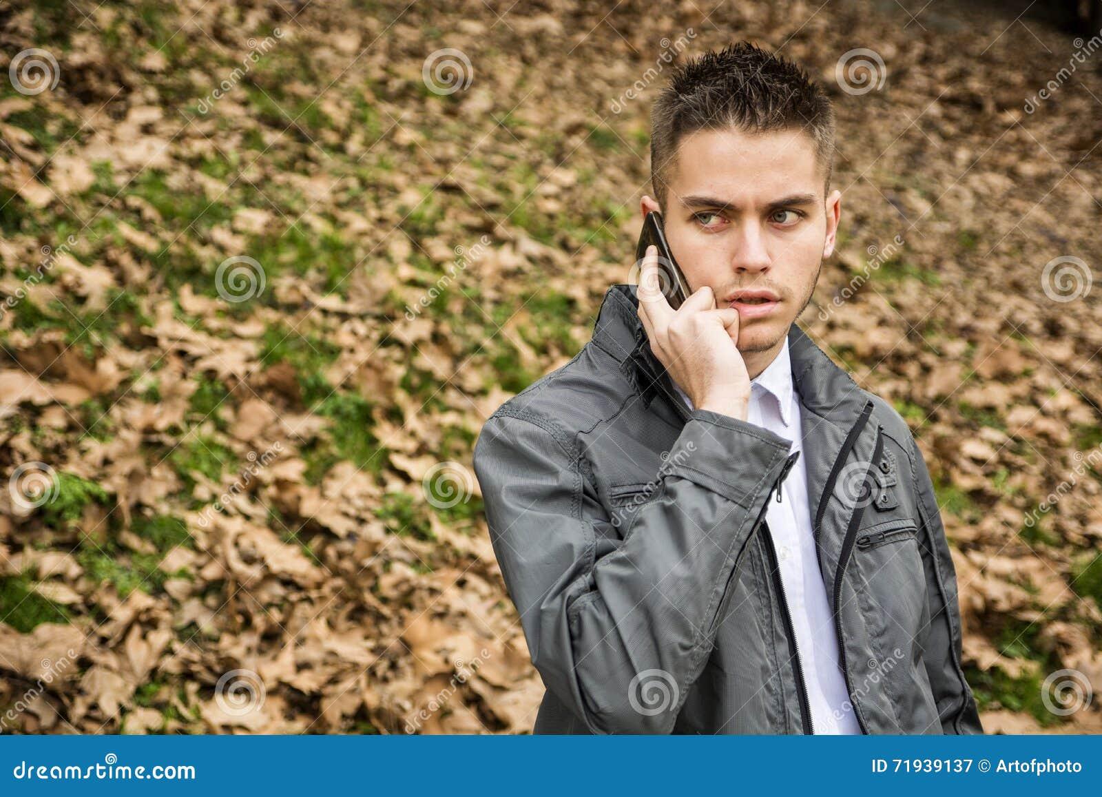 Молодой человек в парке используя сотовый телефон