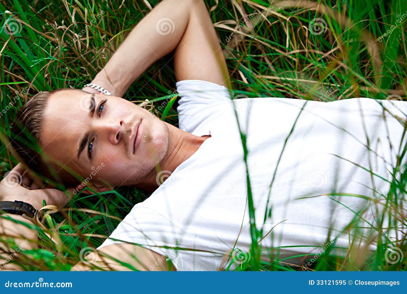 Молодой человек лежа на зеленых gras