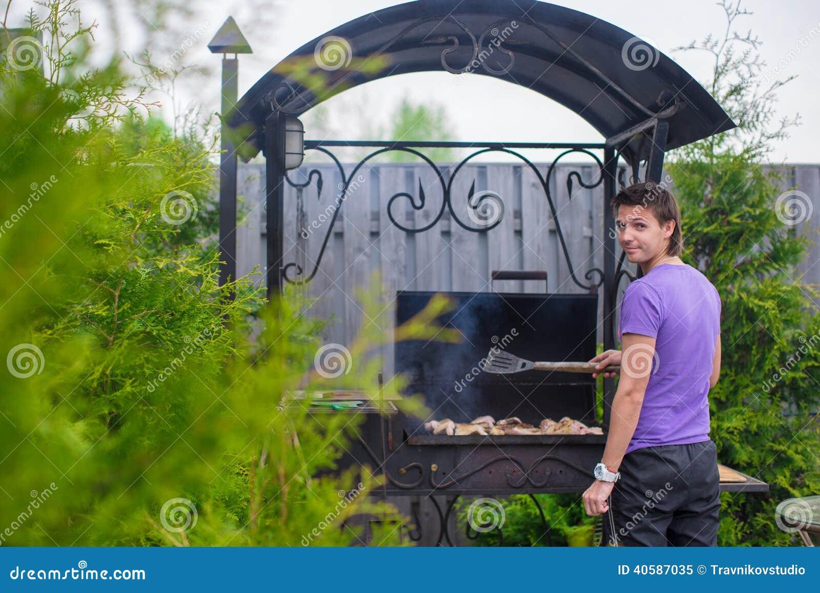 Молодой человек жарит стейки на гриле внешнем в его дворе