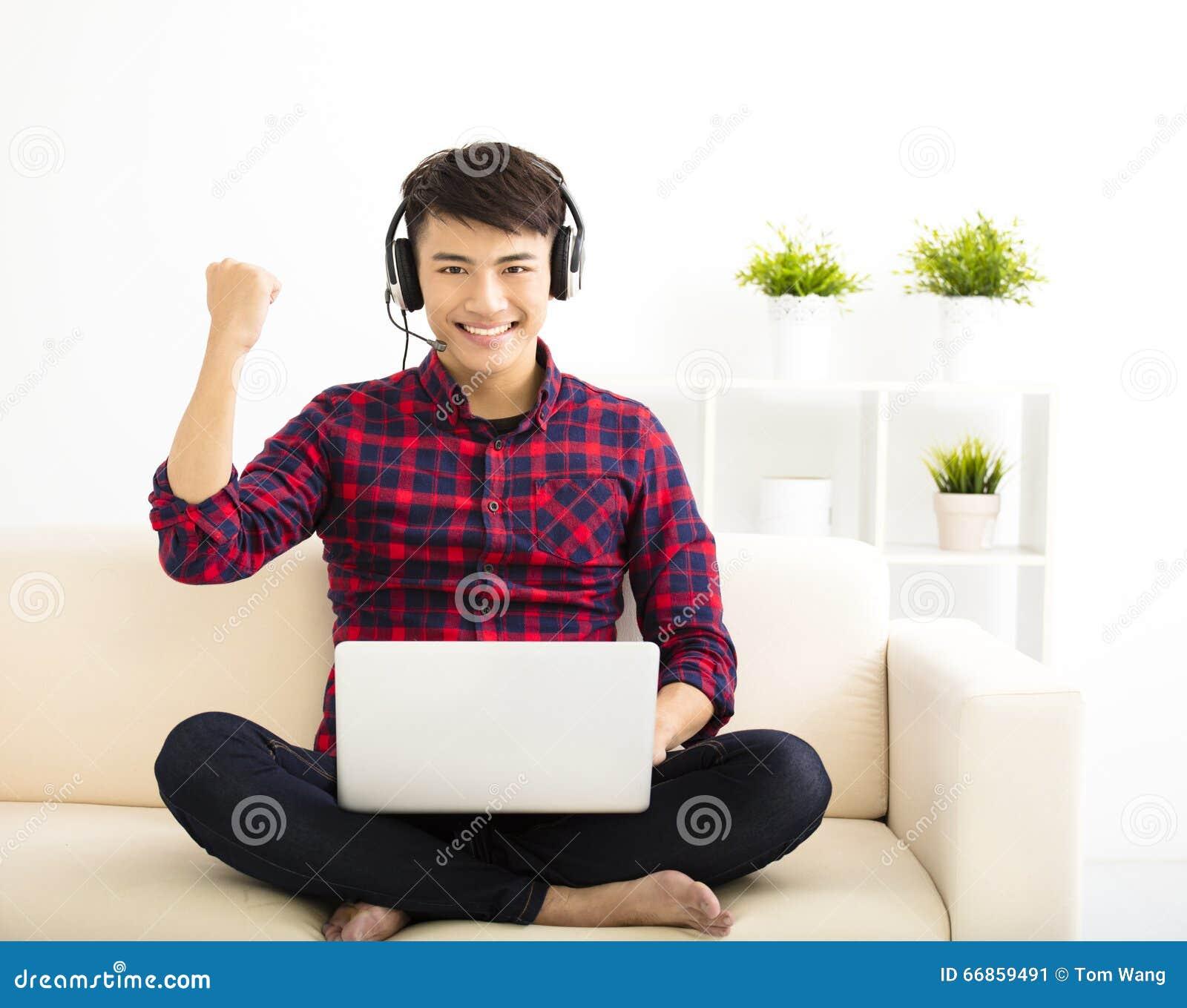 молодой человек используя портативный компьютер с шлемофоном