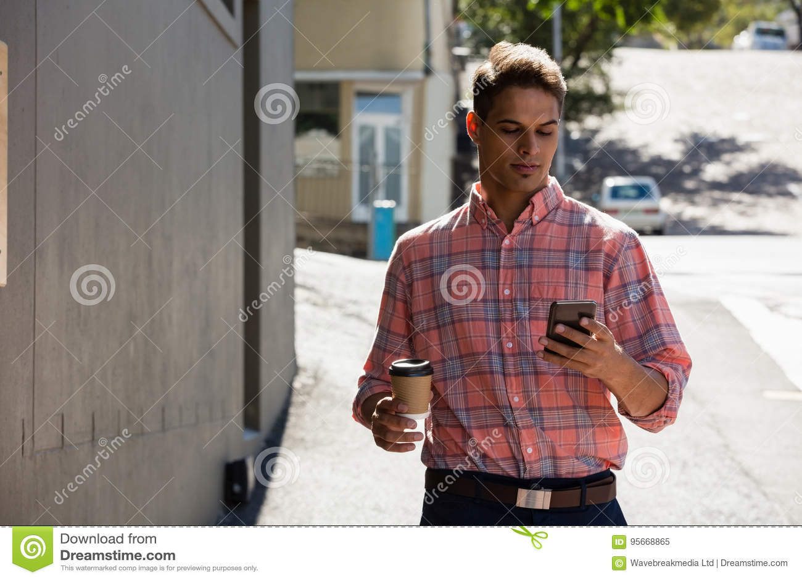Молодой человек используя телефон пока идущ путем строить