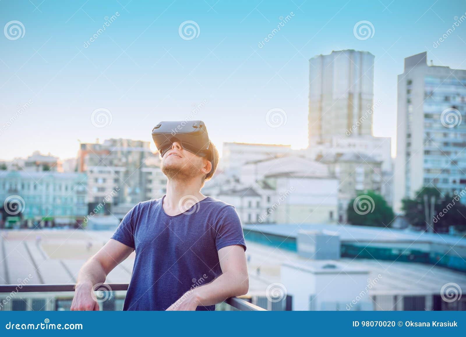 Молодой человек наслаждаясь шлемофоном стекел виртуальной реальности или зрелища 3d стоя против предпосылки здания города outdoor