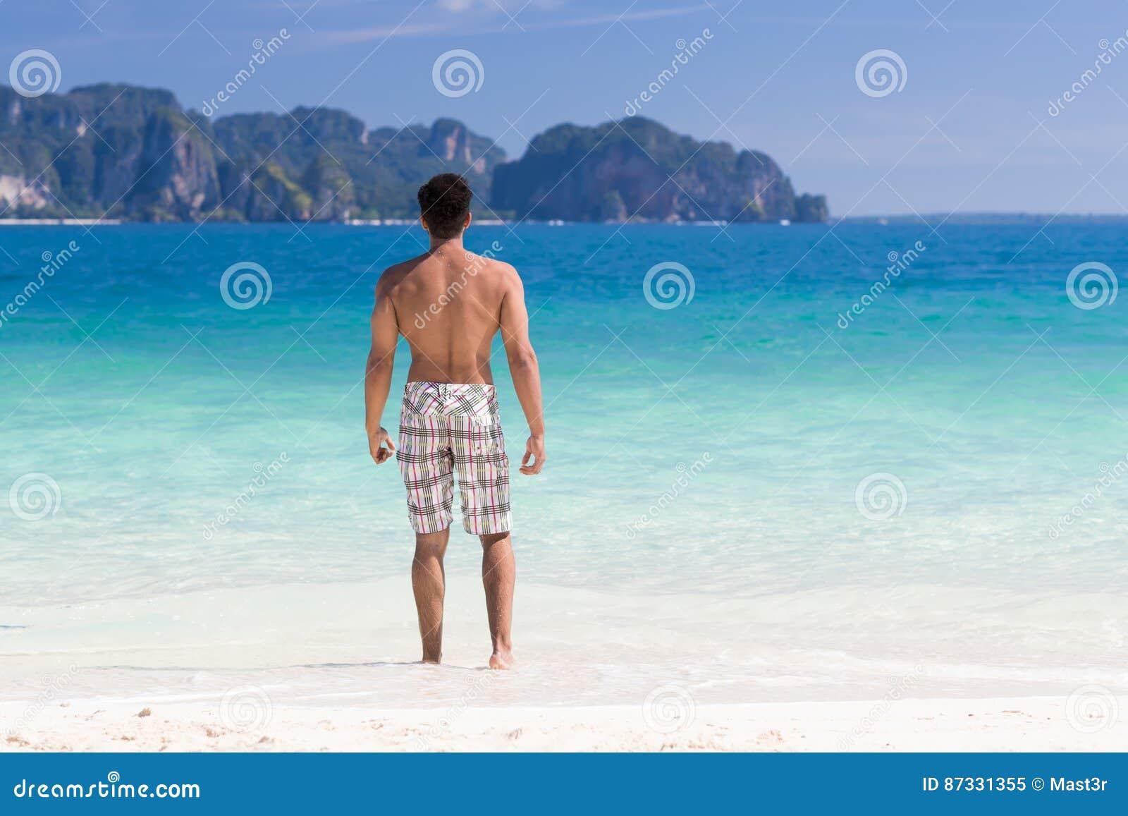 Молодой человек на летних каникулах пляжа, Гай стоя назад открытое море взморья