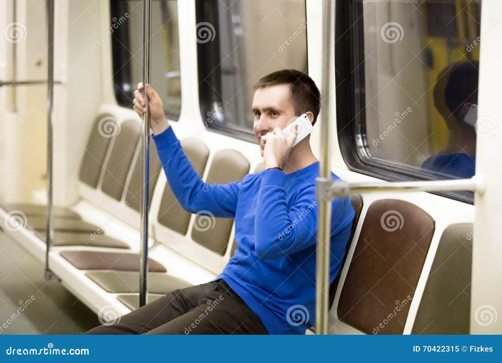 Молодой человек на мобильном телефоне в метро