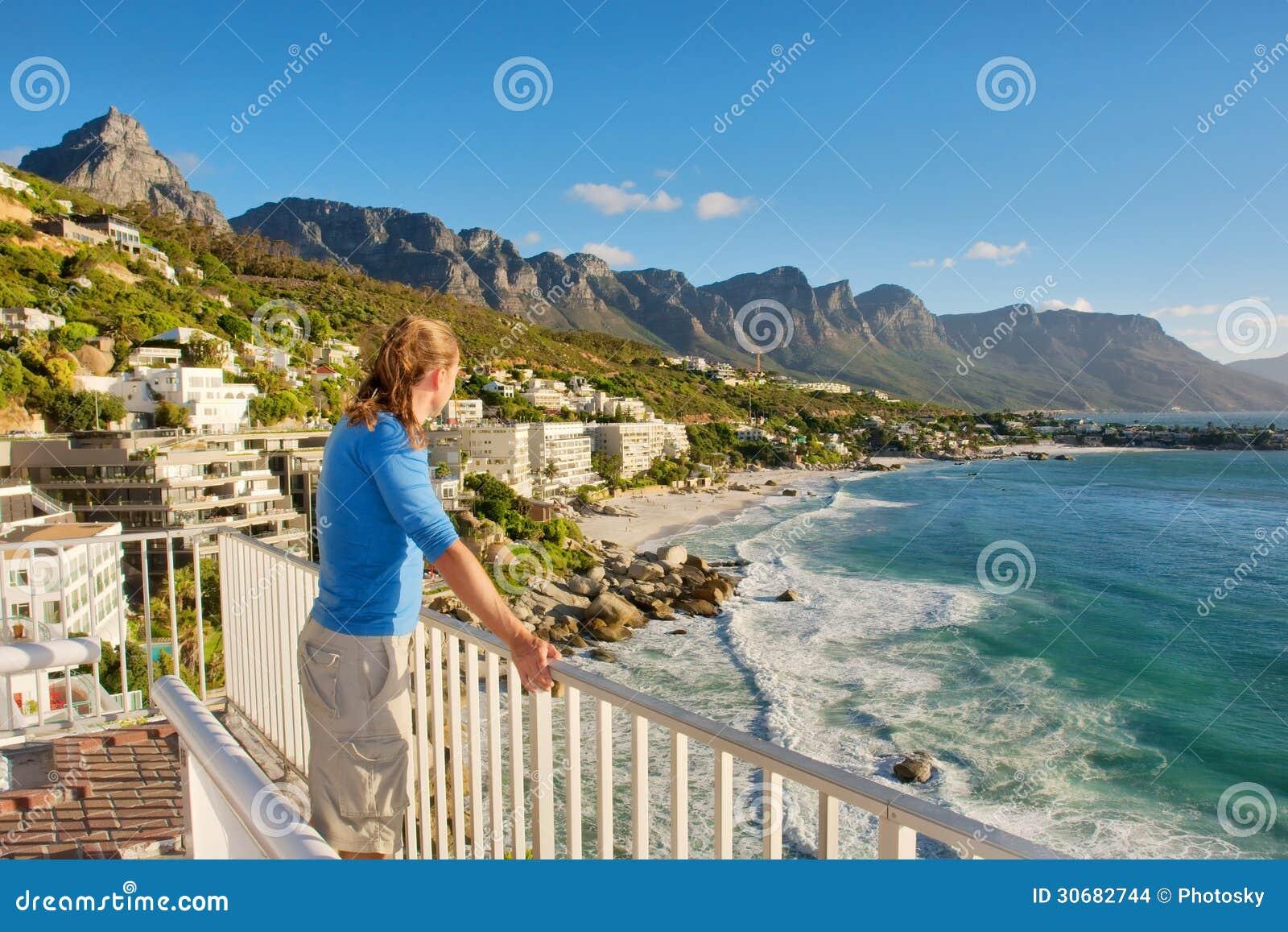 Молодой человек на террасе смотрит панораму пляжа