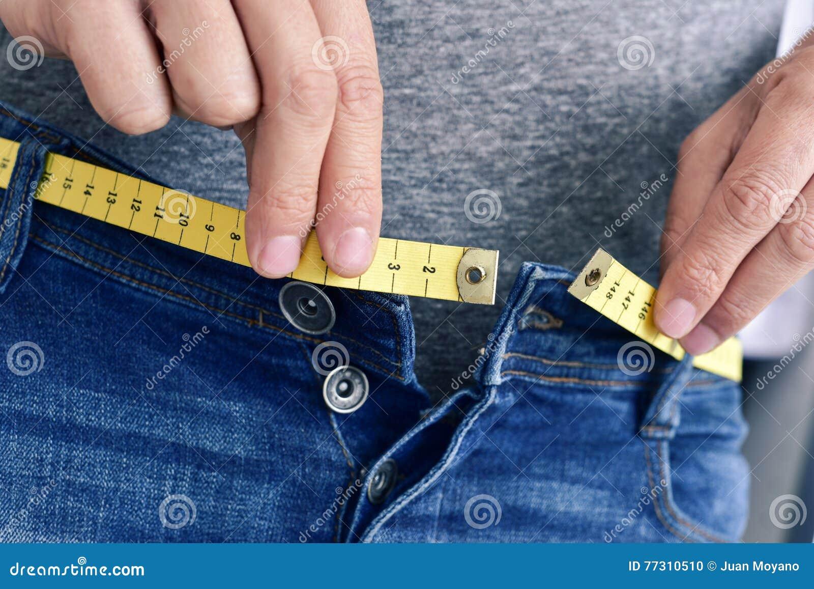 Молодой человек пробуя прикрепить его брюки