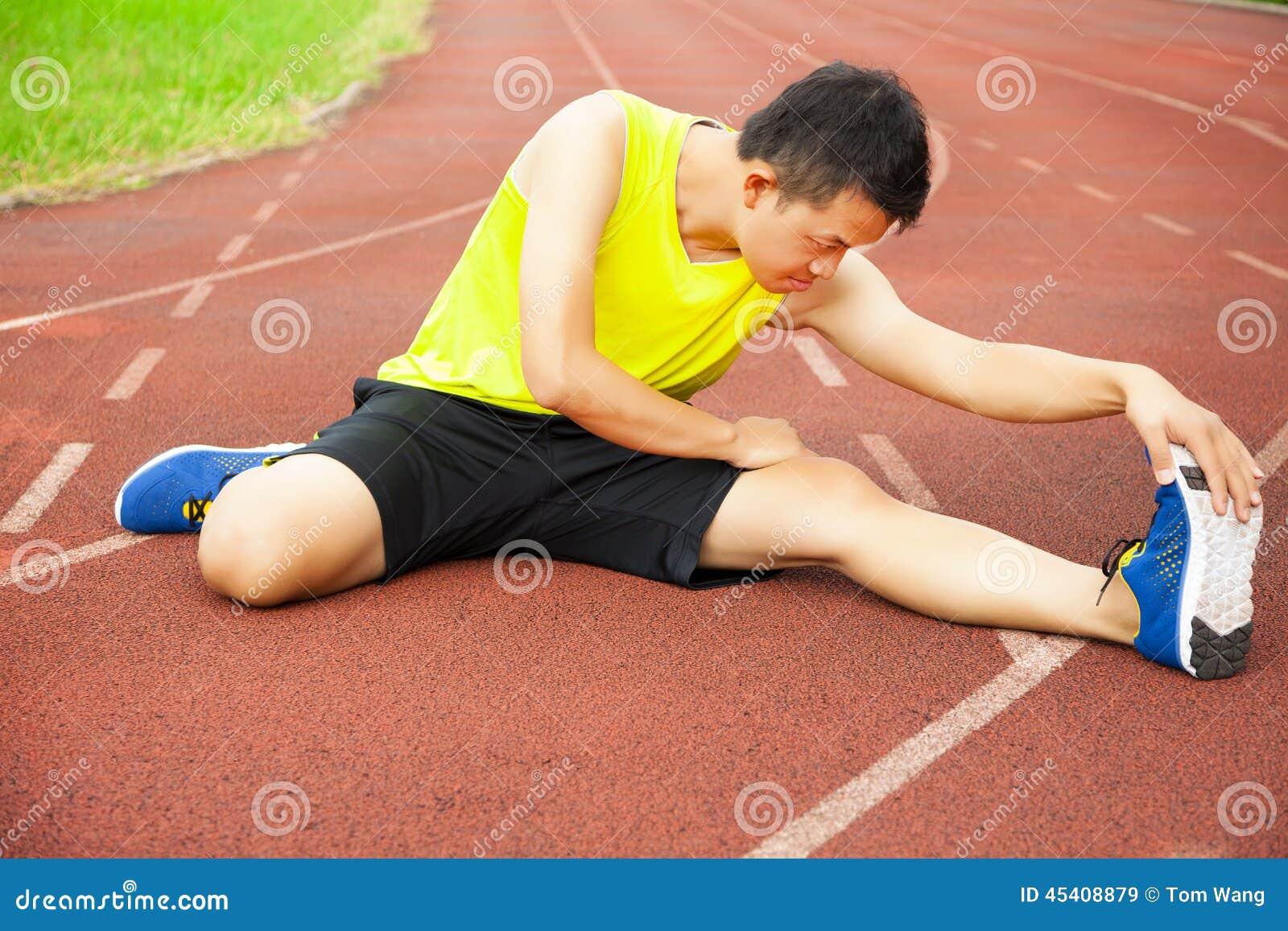 Молодой человек сидя на следе и протягивая его ногу
