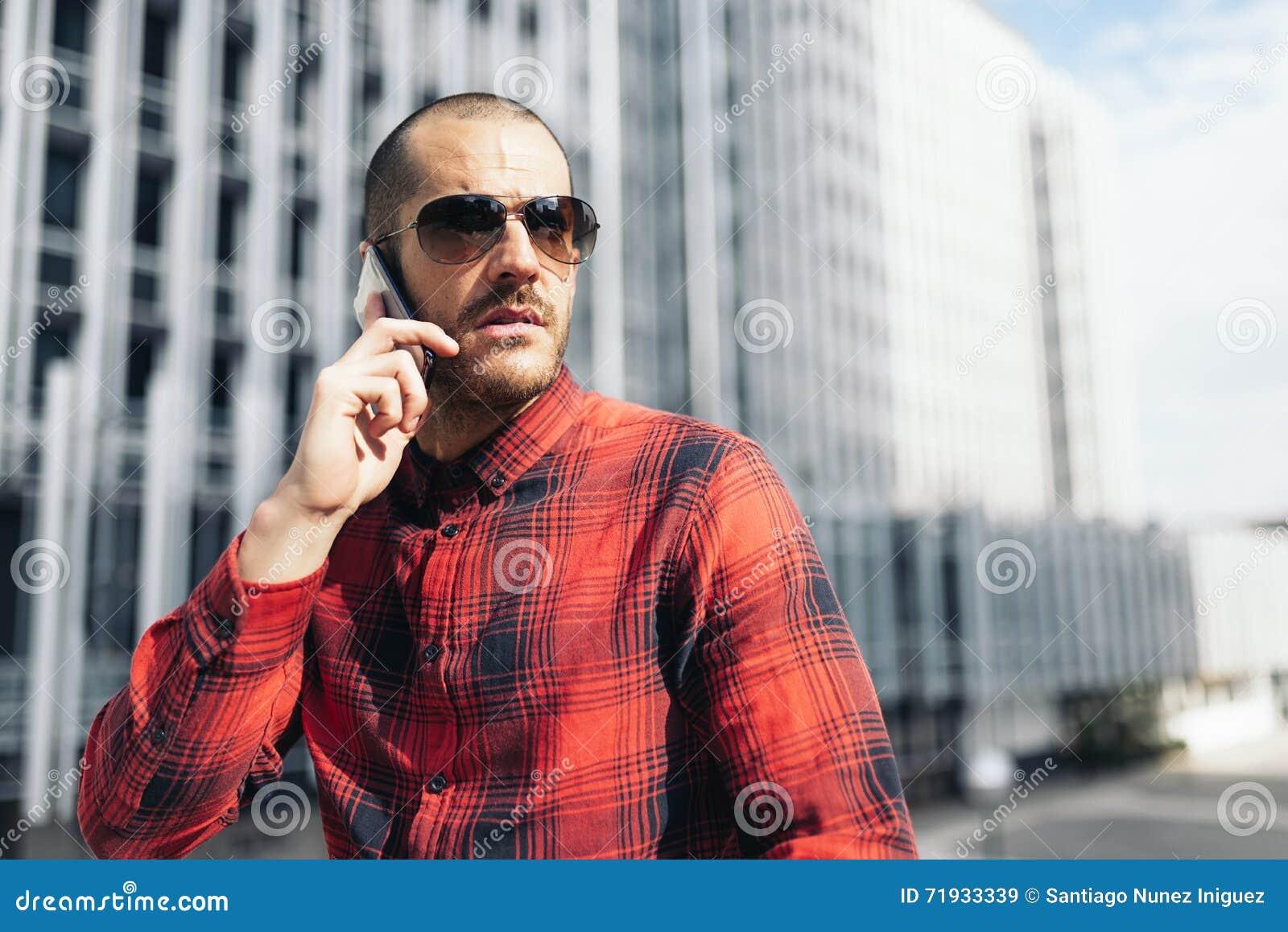 Молодой человек с мобильным телефоном в городе