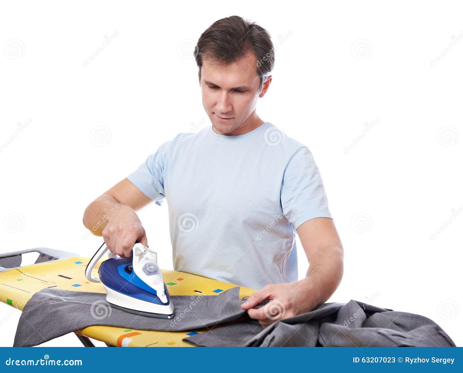 Молодой человек утюжа его серые изолированные брюки