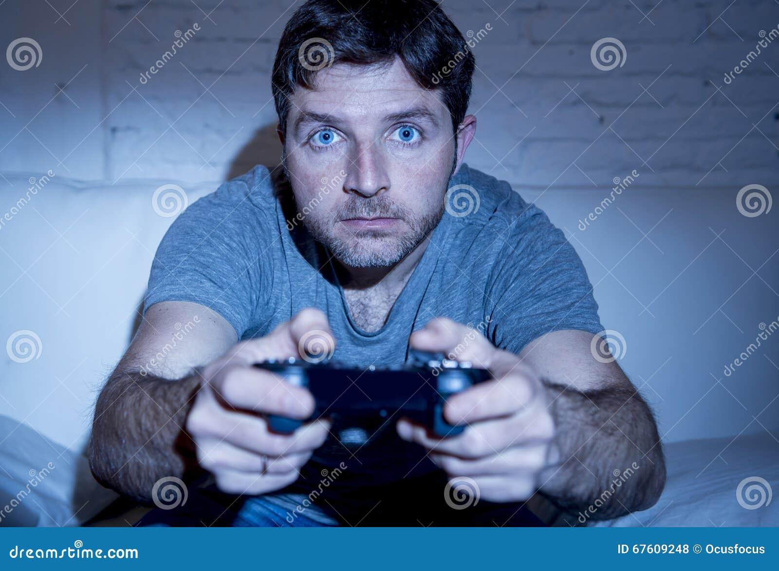 Молодой excited человек дома сидя на софе живущей комнаты играя видеоигры используя кнюппель дистанционного управления