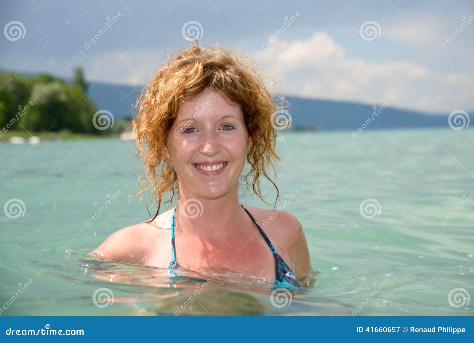 Молодой redhead и естественный купать в озере