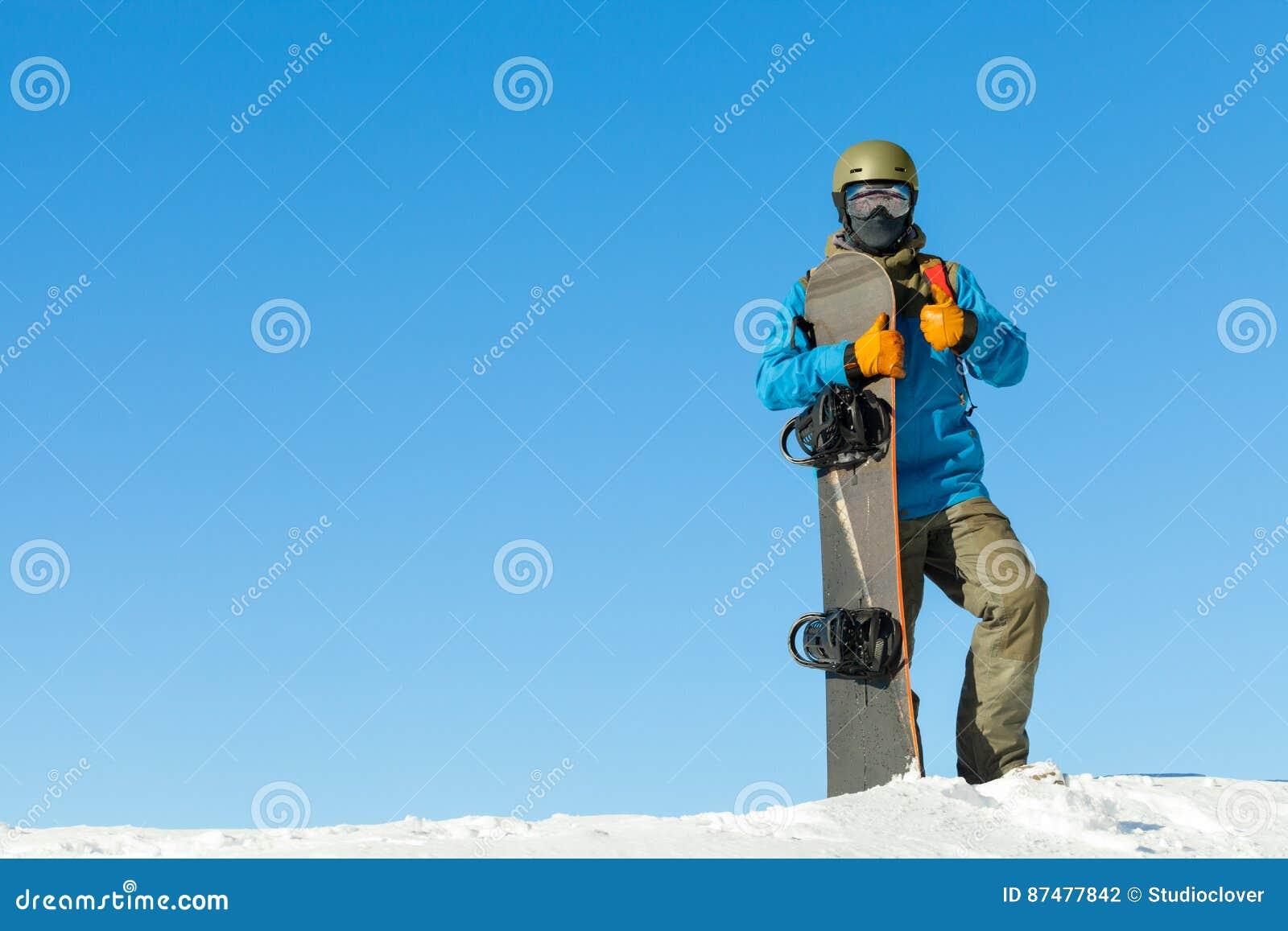 Молодой snowboarder в шлеме вверху очень снежная гора с красивым голубым небом на предпосылке