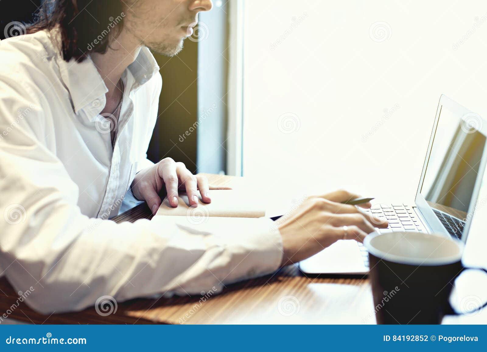 Молодые бизнесмен или студент, длинные волосы, работая сочинительство на клавиатуре около окна с открытой компьтер-книжкой