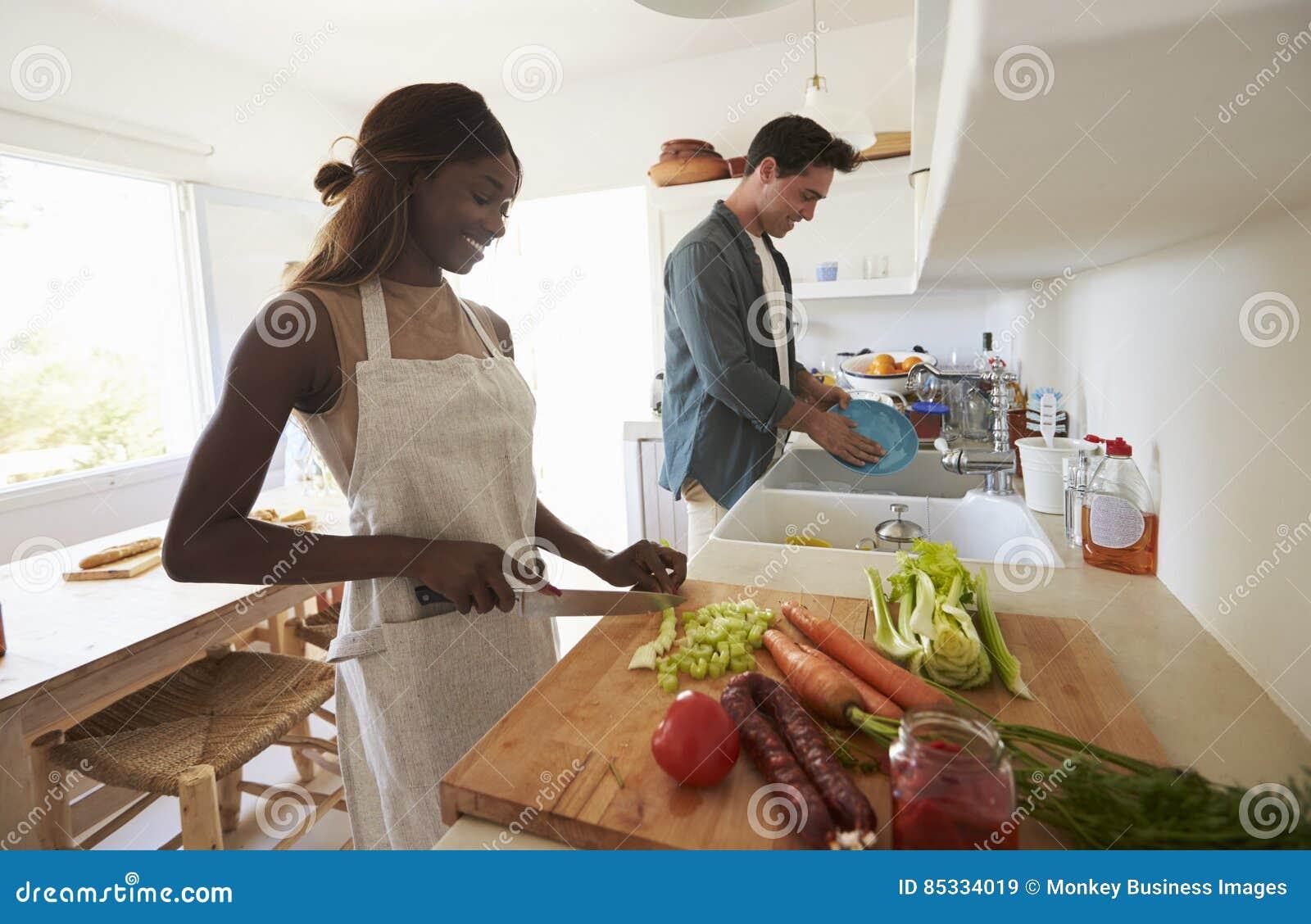 Молодые взрослые пары подготавливая еду для официальныйа обед