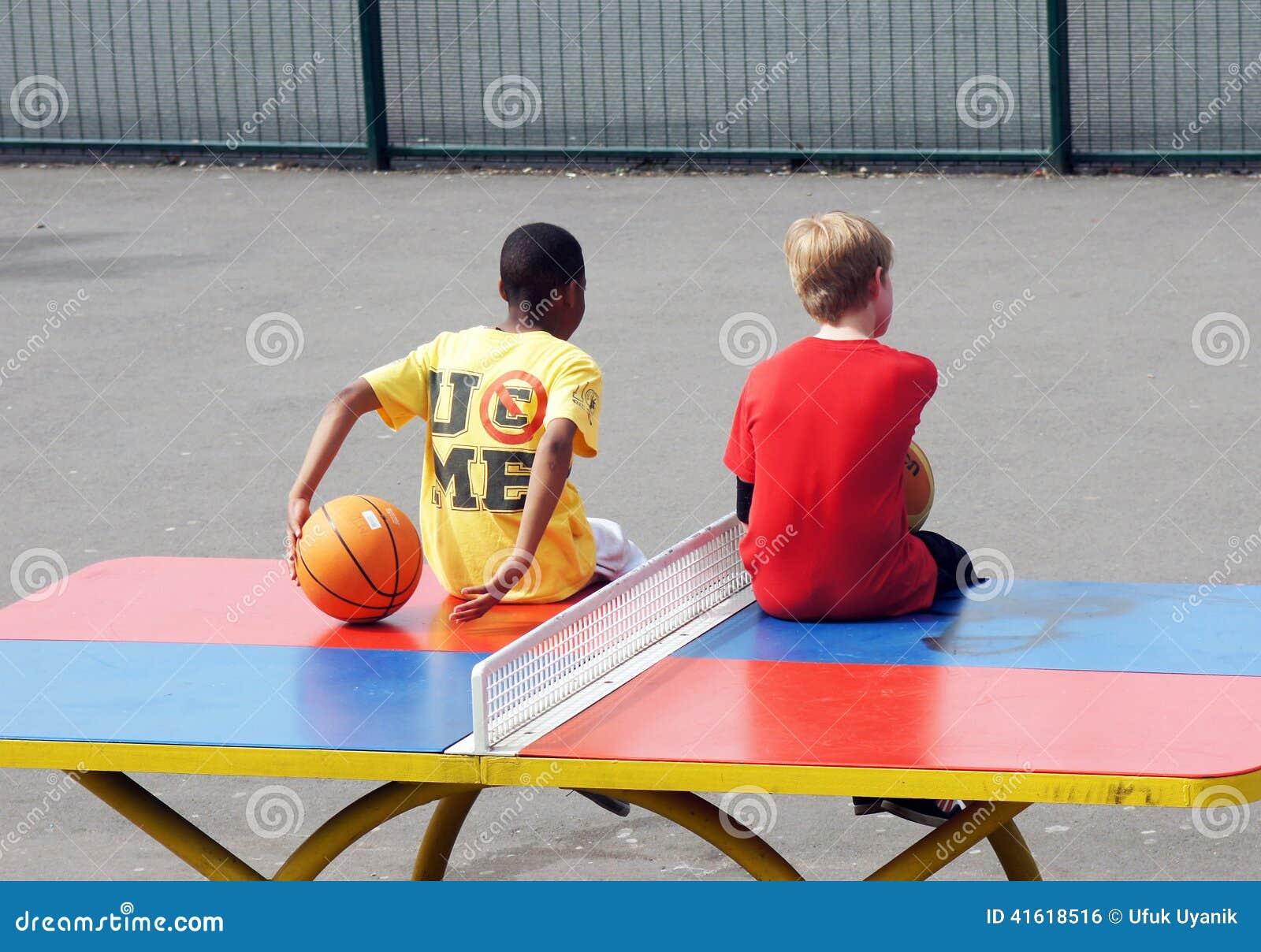 Молодые мальчики сидят на таблице настольного тенниса