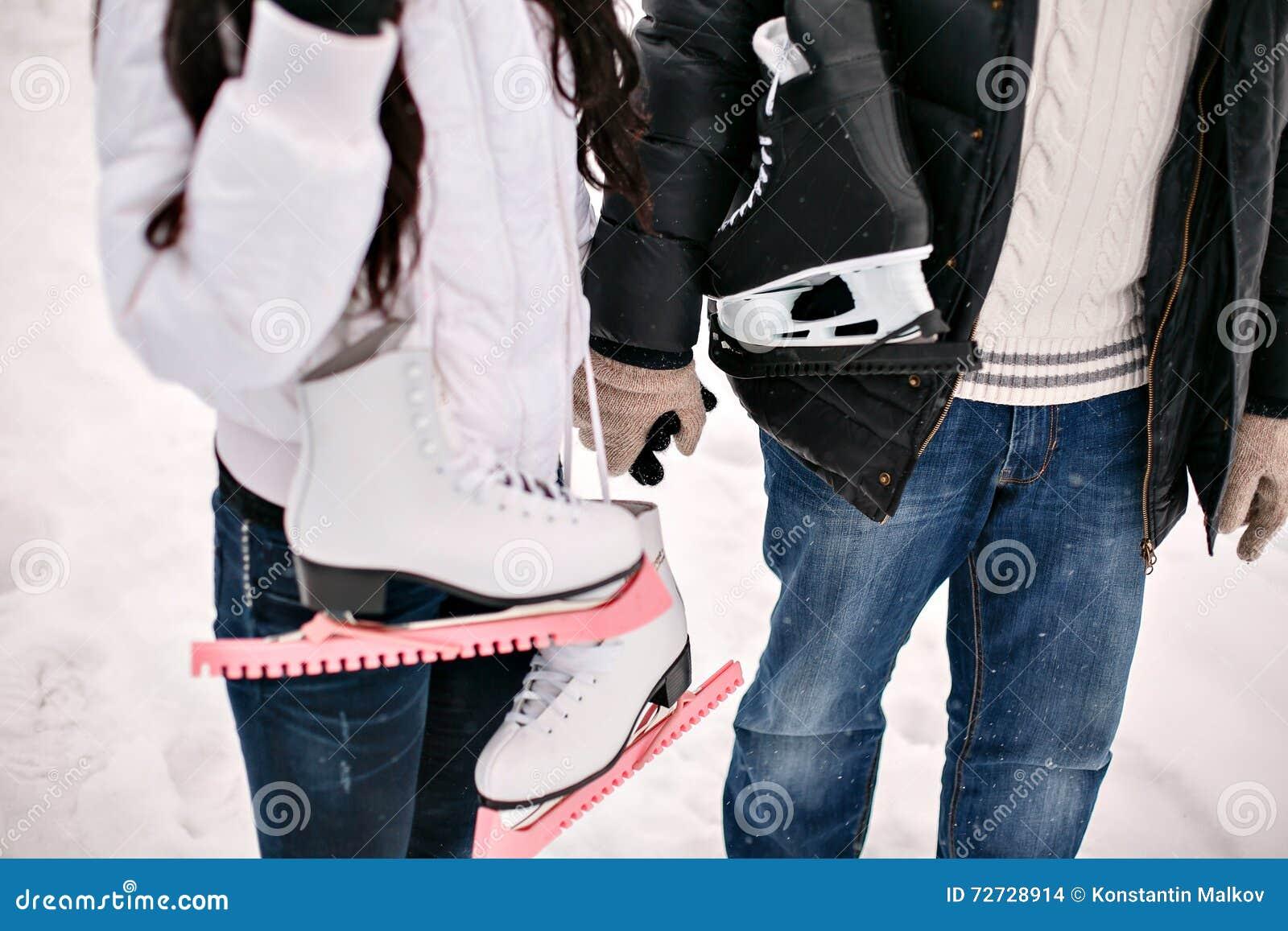 Молодые пары влюбленности держа его коньки на плече зима снежка положения праздников мальчика