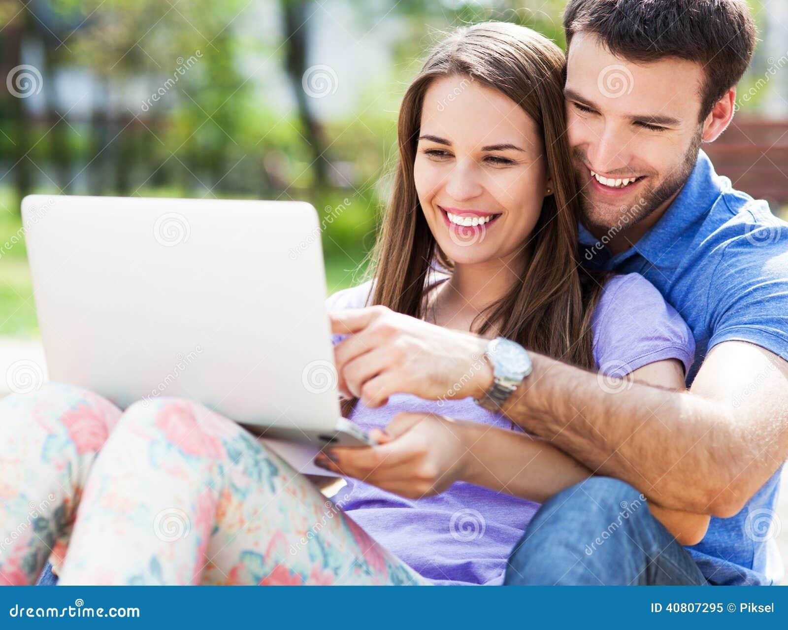 Молодые пары используя компьтер-книжку outdoors