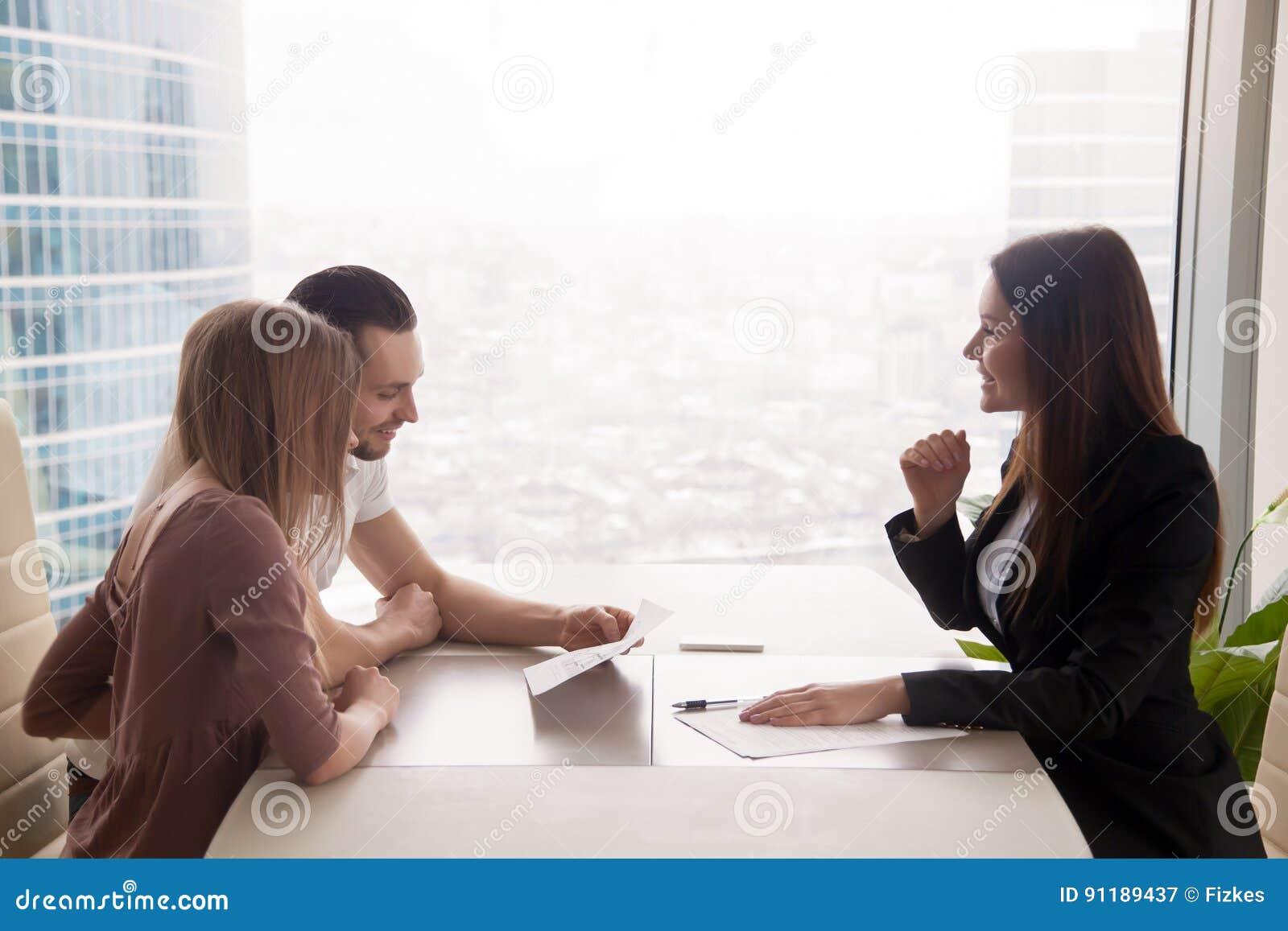 Молодые пары и женский маклер имущества обсуждая свойство для sa