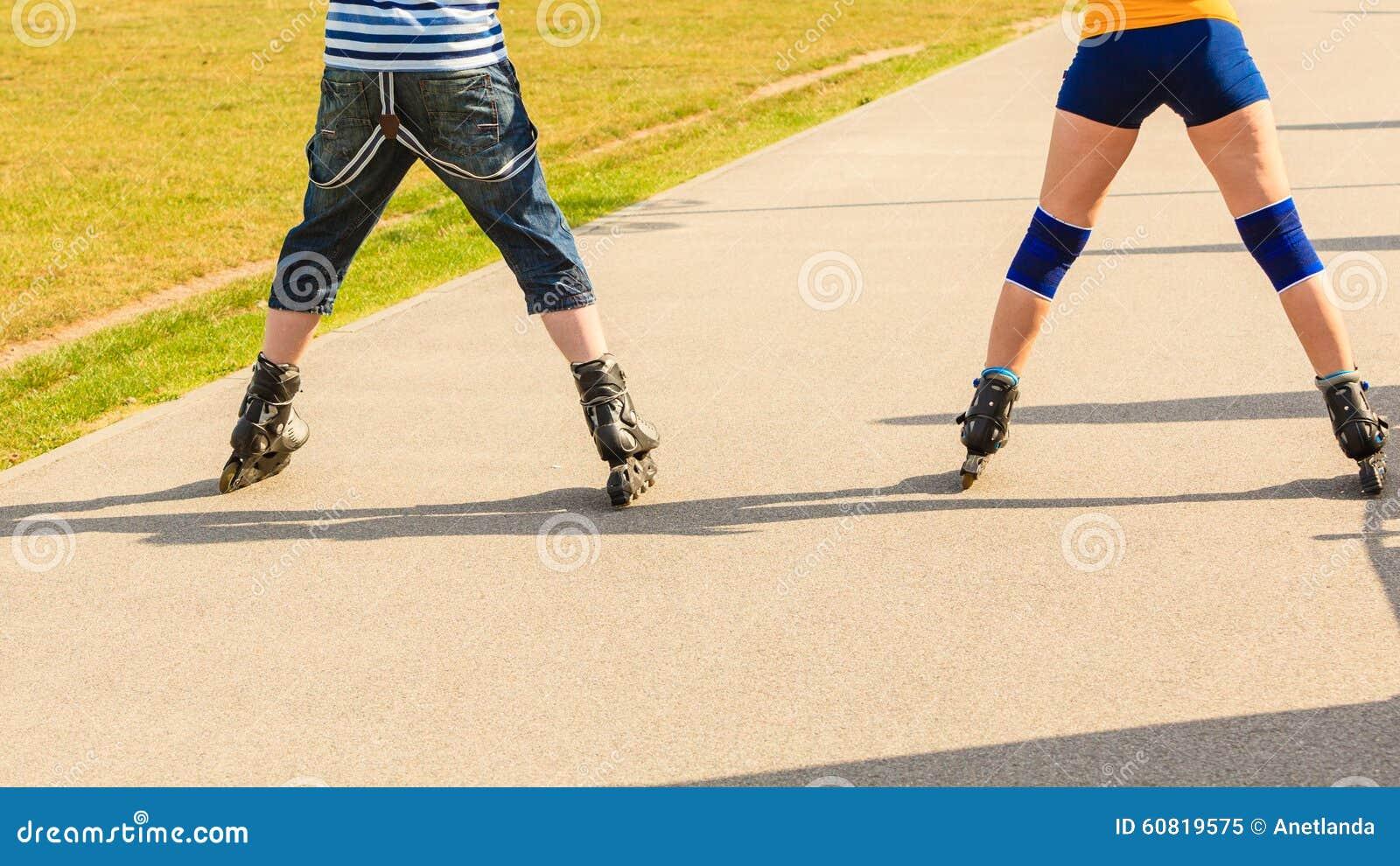 Молодые пары на коньках ролика ехать outdoors
