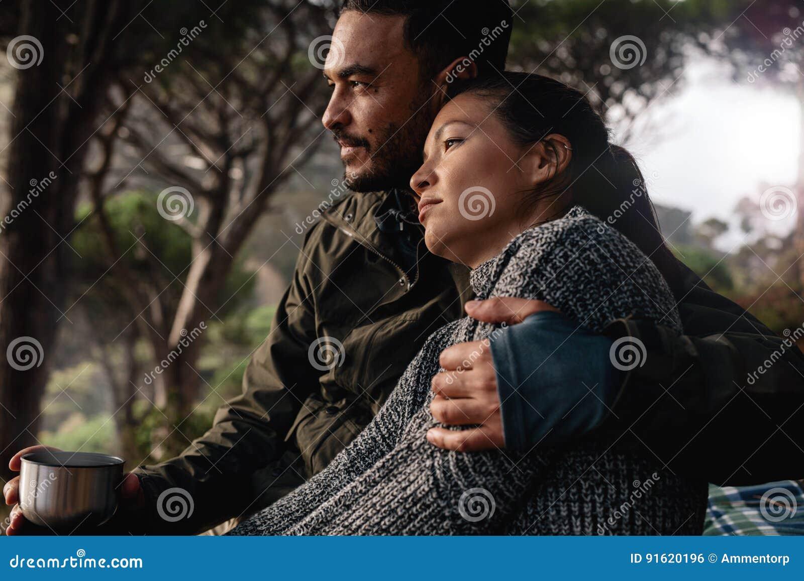 Молодые пары отдыхая outdoors с чашкой кофе