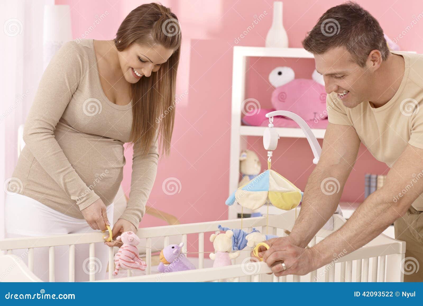 Молодые пары подготавливая детскую кроватку