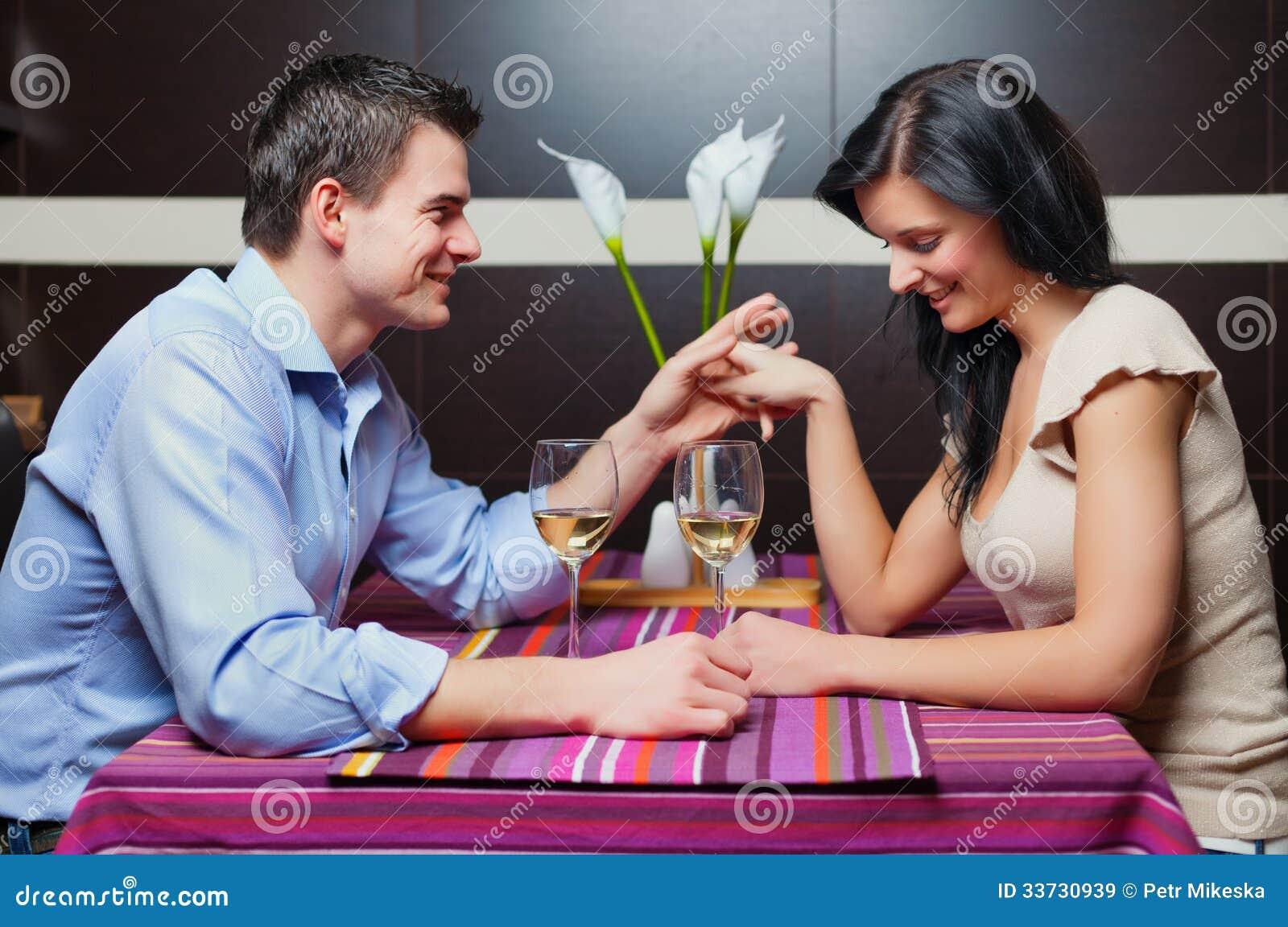 Молодые пары сидя в ресторане и flirting