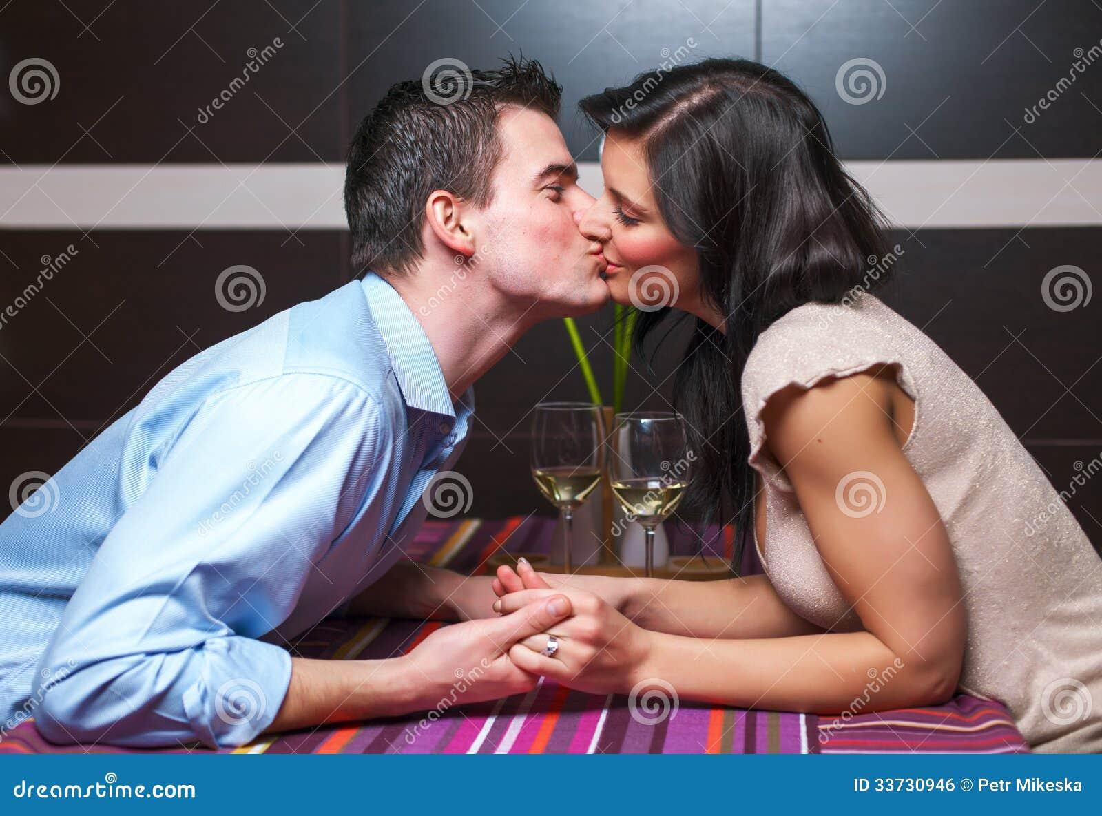 Молодые пары целуя в ресторане