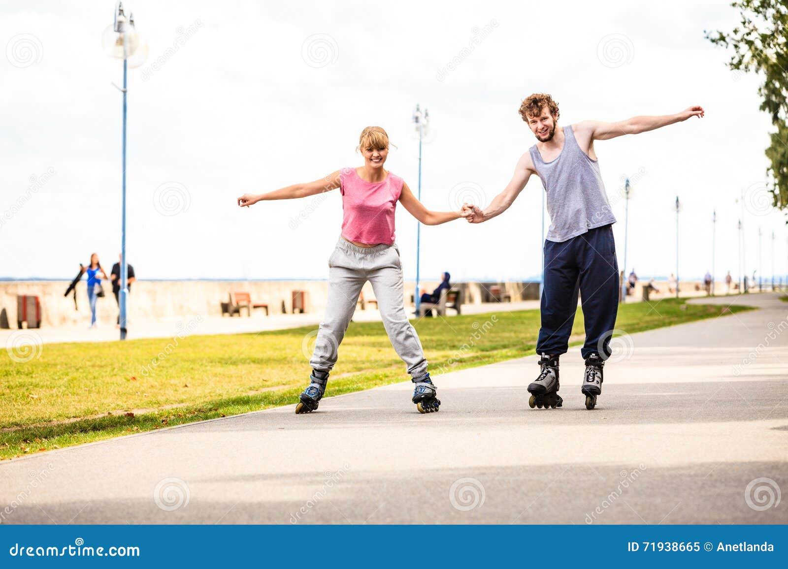 Молодые пары rollerblading в парке держа руки