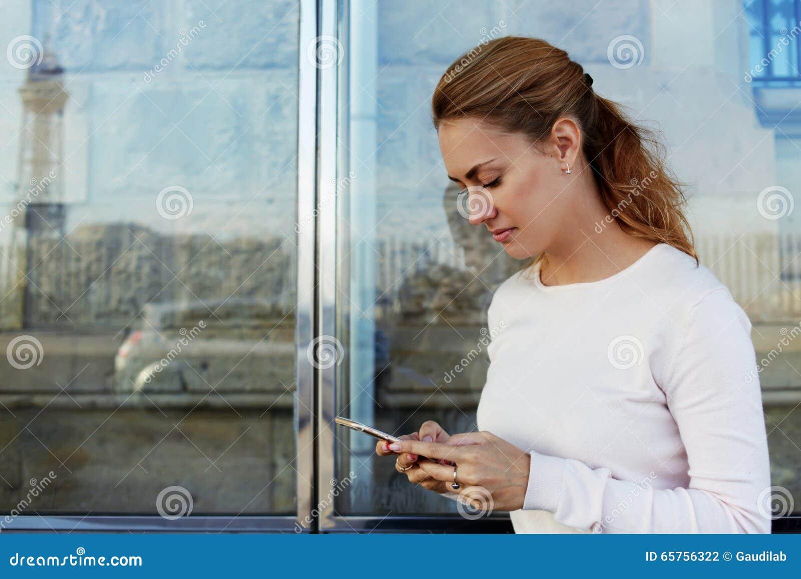 Молодые привлекательные данные по чтения женщины через сеть на мобильном телефоне пока ждущ автомобиль на станции,