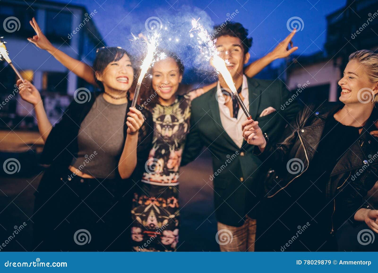 Молодые друзья имея партию ночи с бенгальскими огнями