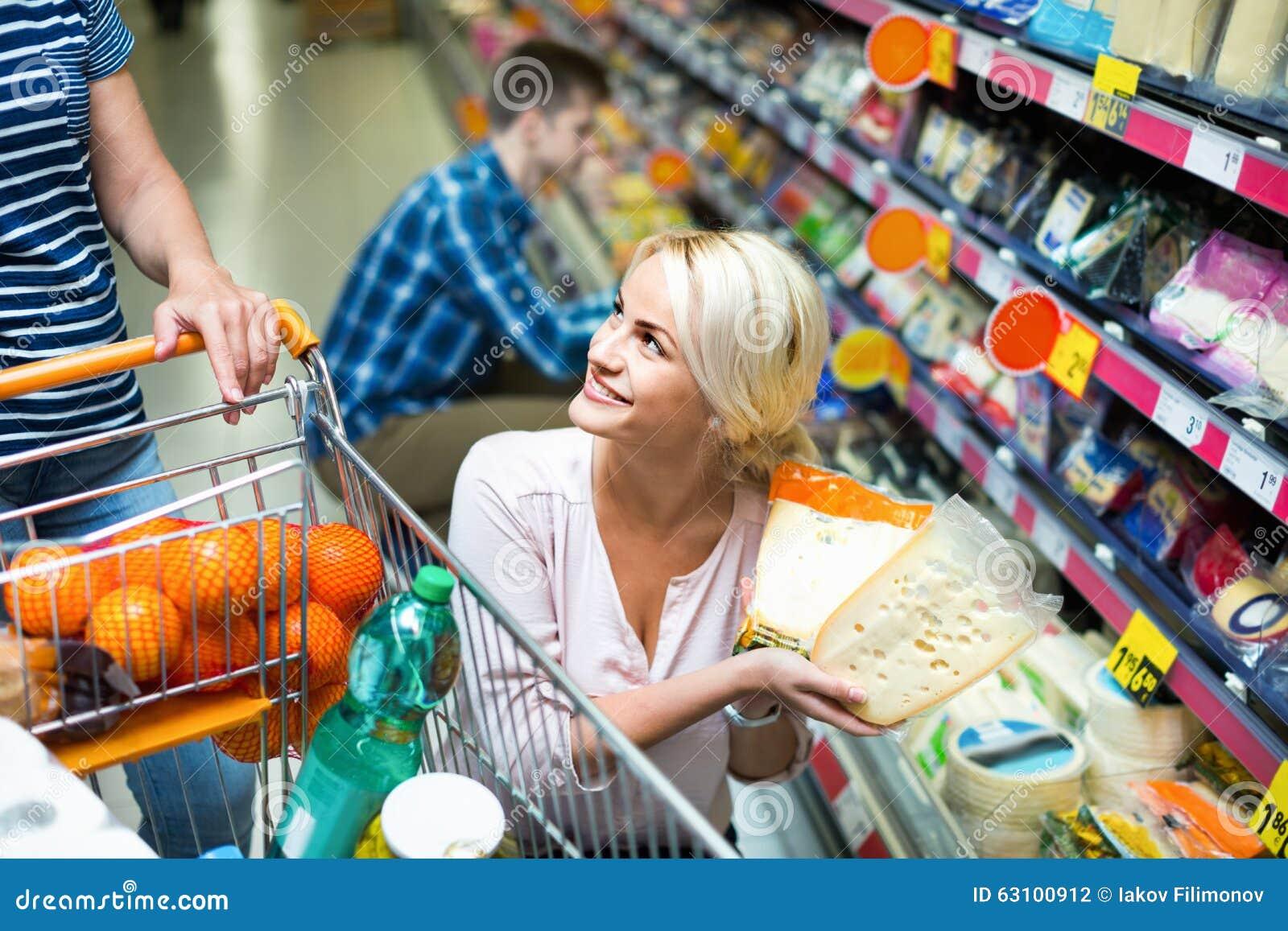 Молодые супруги покупая чеддер в разделе сыра