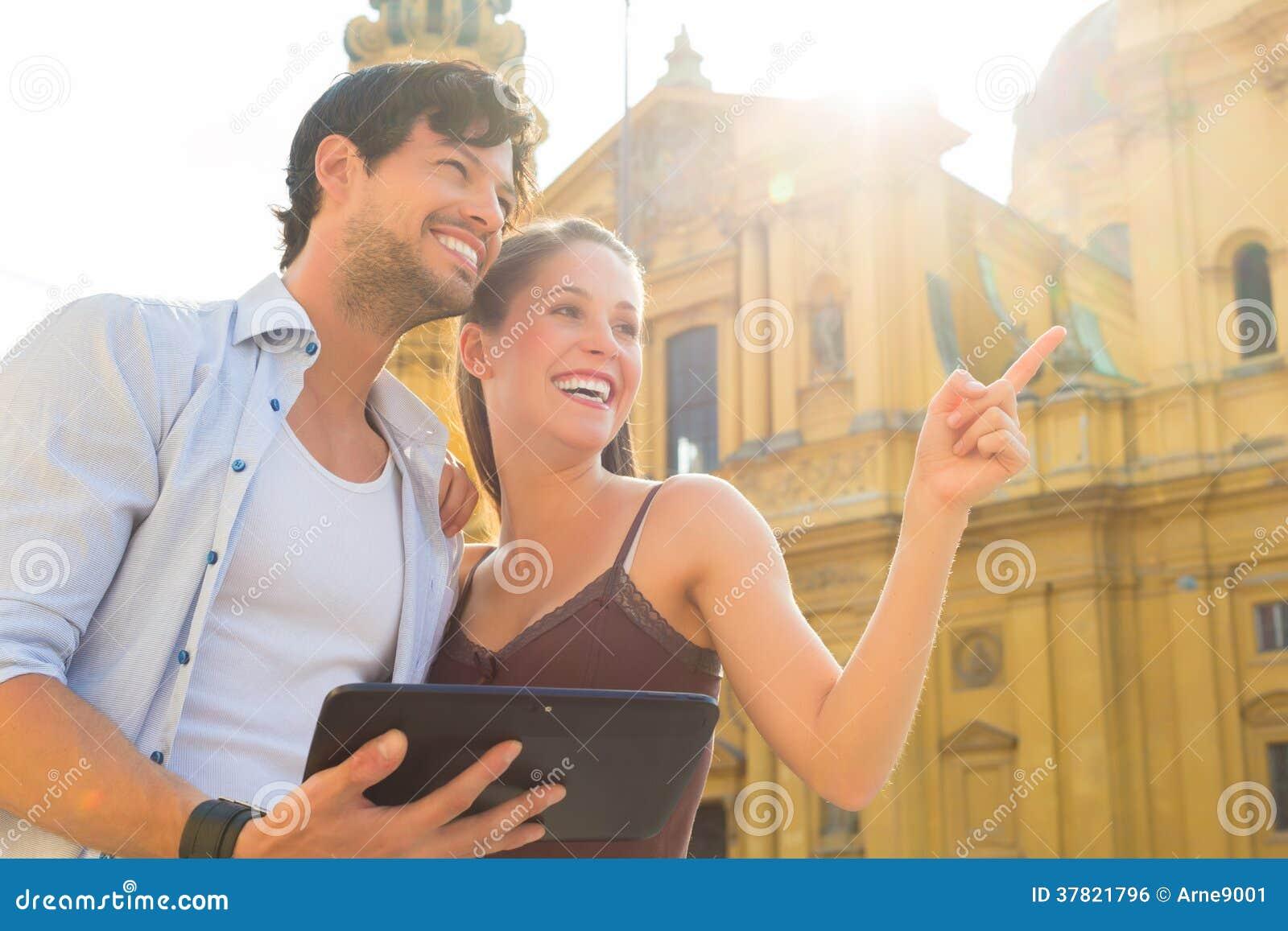 Молодые туристы в городе с планшетом