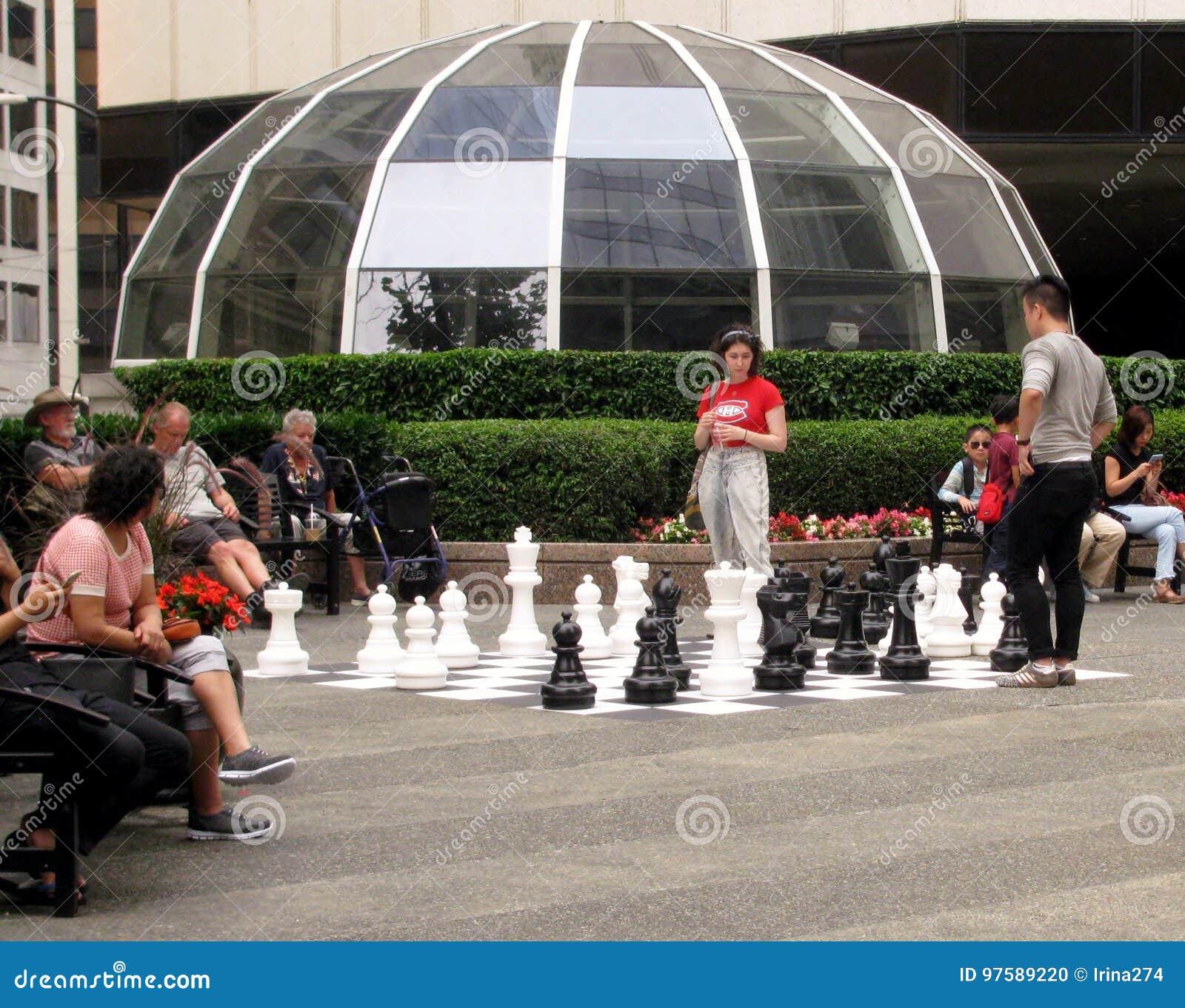 Молодые люди играя шахмат около центра ` s Тихий Океан Ванкувера ДО РОЖДЕСТВА ХРИСТОВА, Канада