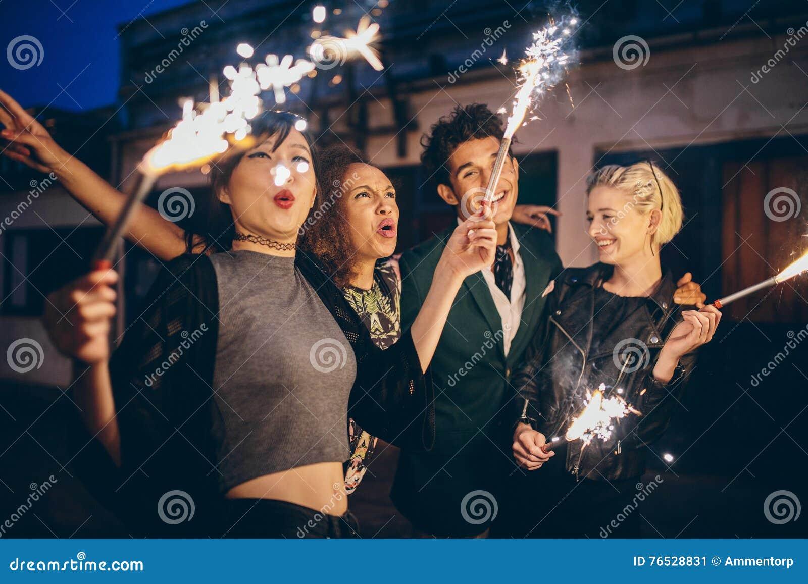 Молодые люди наслаждаясь кануном Новых Годов с фейерверками