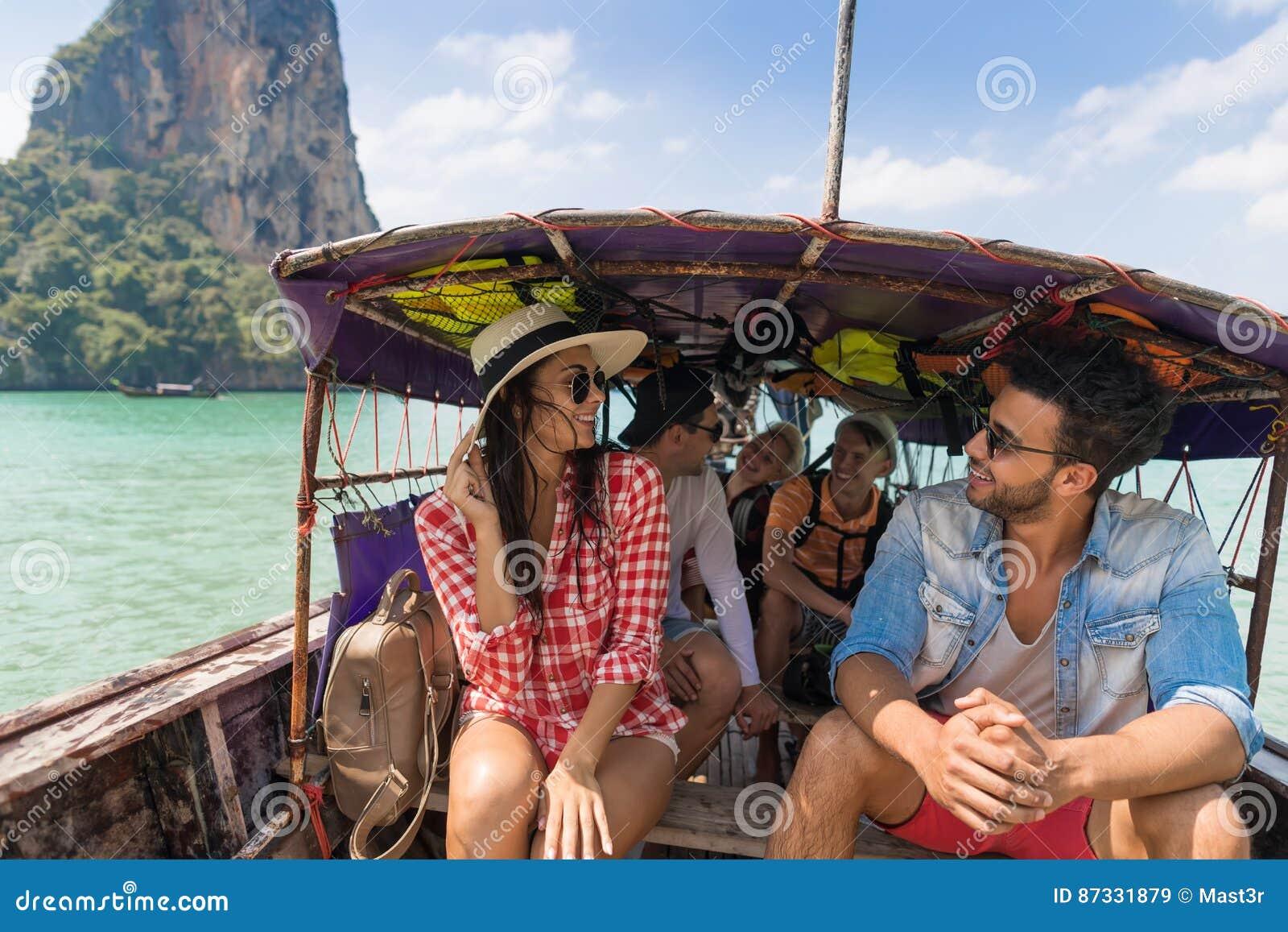Молодые люди отключения перемещения каникул моря друзей океана шлюпки Таиланда длинного хвоста ветрила группы туристского