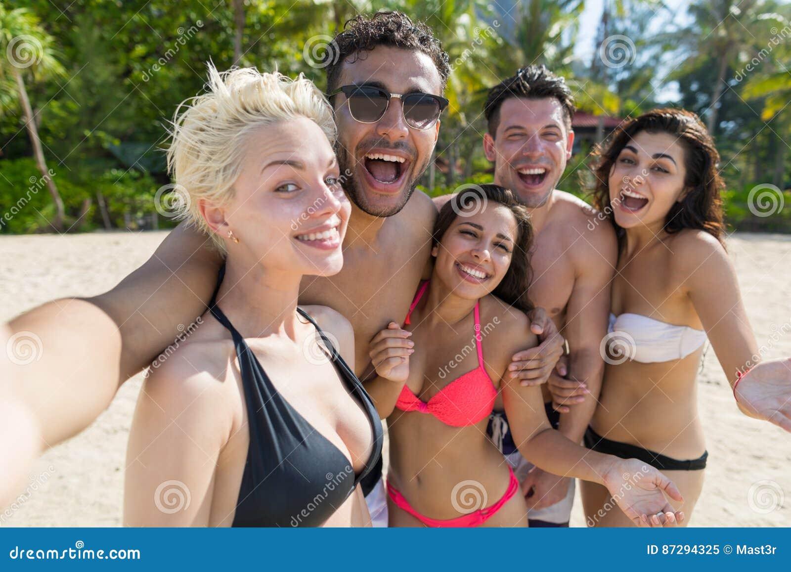 Молодые люди собирает на летние каникулы пляжа, счастливые усмехаясь друзей принимая океан моря фото Selfie