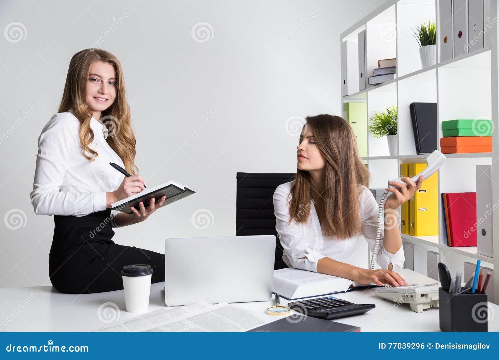2 молодых дамы дела на рабочем месте в белом офисе