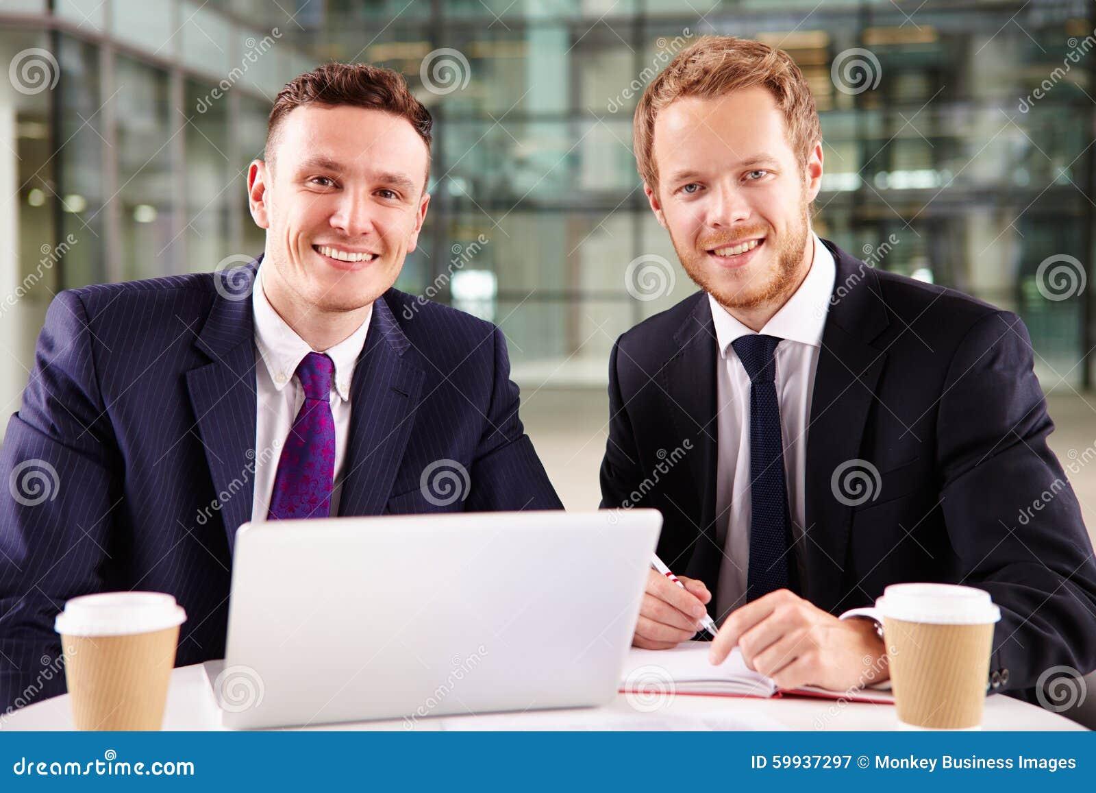 2 молодых бизнесмена имея кофе, используя портативный компьютер