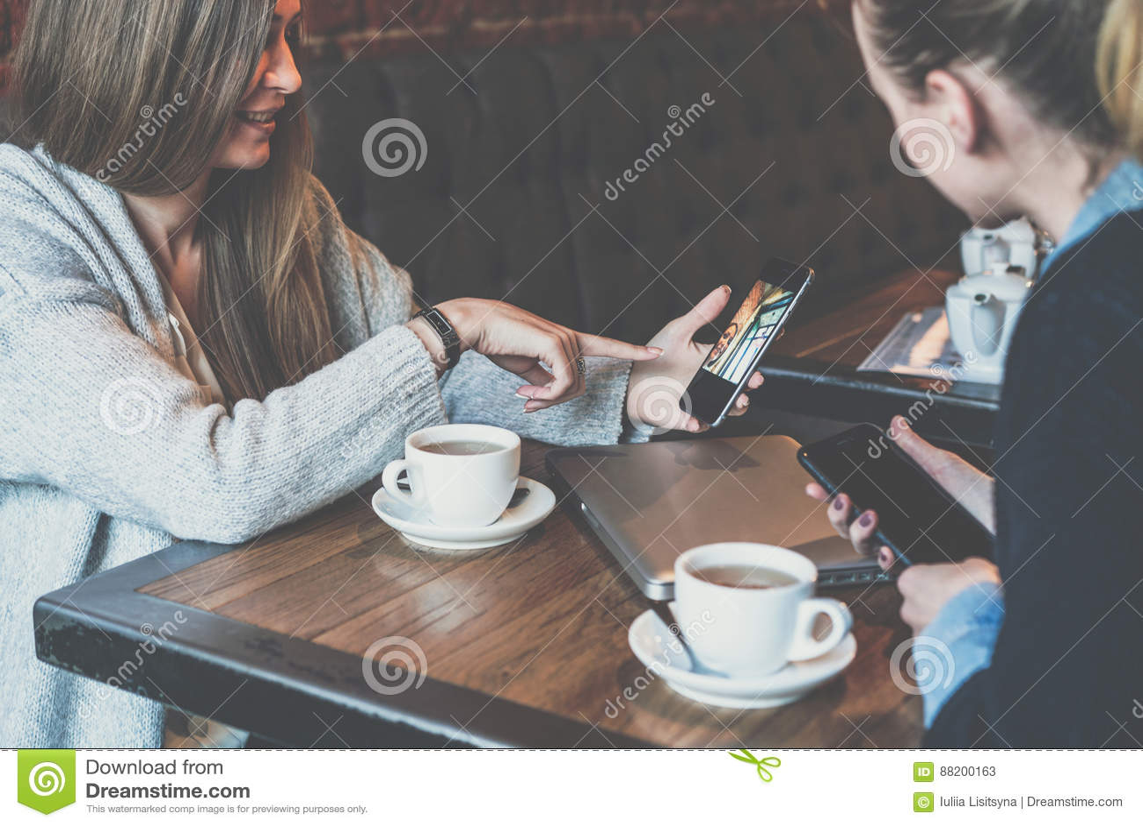 2 молодых бизнес-леди сидя на таблице и используя smartphones Женщина показывая изображение коллеги на экране smartphone