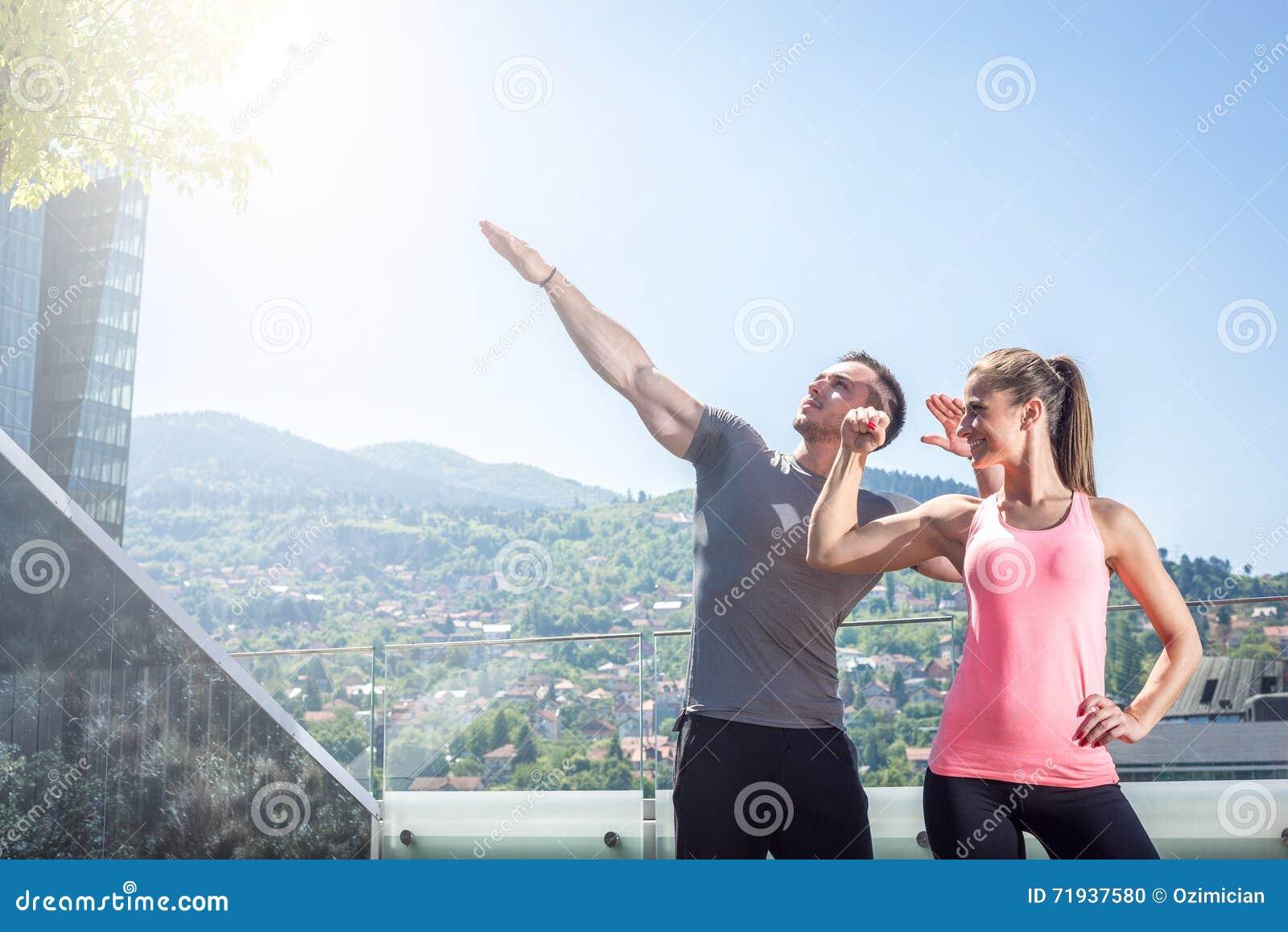 2 молодых взрослых модели фитнеса представляя на крыше